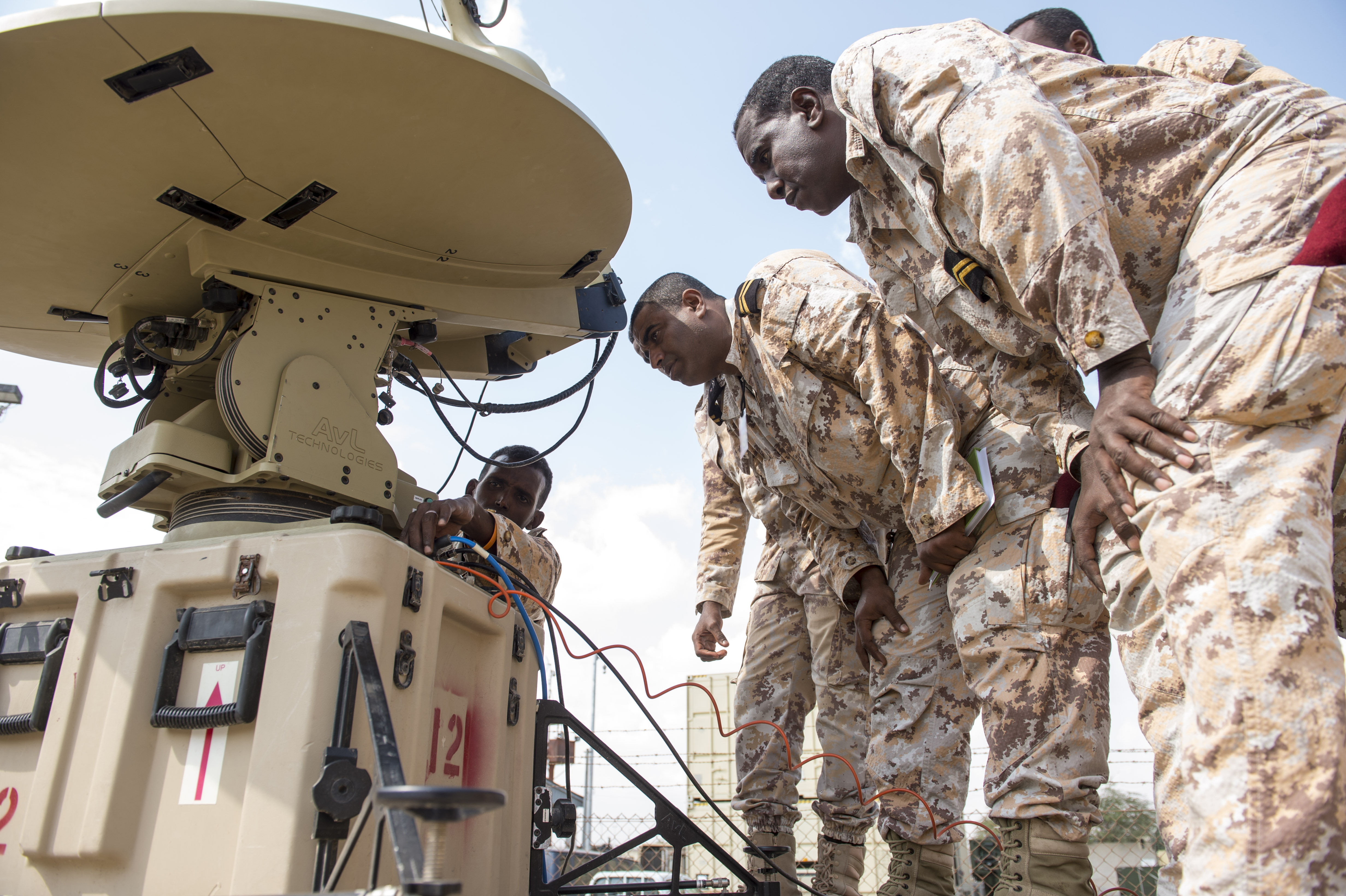 Djibouti Armed Forces (FAD) members watch as another FAD member checks the cable connections on an antenna during a military-to-military exchange course with U.S. Soldiers assigned to the Combined Joint Task Force - Horn of Africa (CJTF-HOA) Communications Directorate, at Camp Lemonnier, Djibouti, Jan. 9, 2018. Throughout a two-week period, communications experts advised Djiboutian service members on how to set up, operate, maintain, and troubleshoot network equipment to increase communication capabilities between African Union Mission in Somalia forces. (U.S. Air Force photo illustration by Staff Sgt. Timothy Moore)