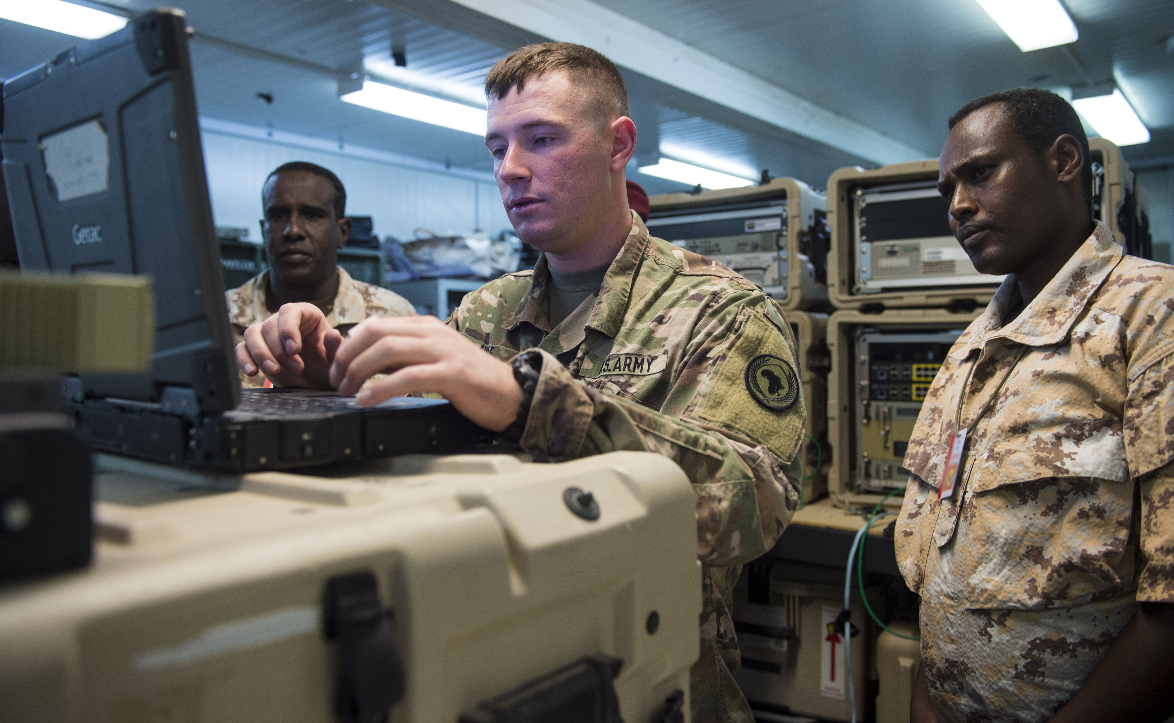 U.S. Army Spc. Taylor Noble, a multisystem transmission operator and maintainer assigned to the Combined Joint Task Force - Horn of Africa (CJTF-HOA) Communications Directorate, shows members of the Djibouti Armed Forces (FAD) how to acquire a satellite signal through using an antenna during a military-to-military exchange course at Camp Lemonnier, Djibouti, Jan. 8, 2018. Throughout a two-week period, communications experts advised Djiboutian service members on how to set up, operate, maintain, and troubleshoot network equipment to increase communication capabilities between African Union Mission in Somalia forces. (U.S. Air Force photo illustration by Staff Sgt. Timothy Moore)