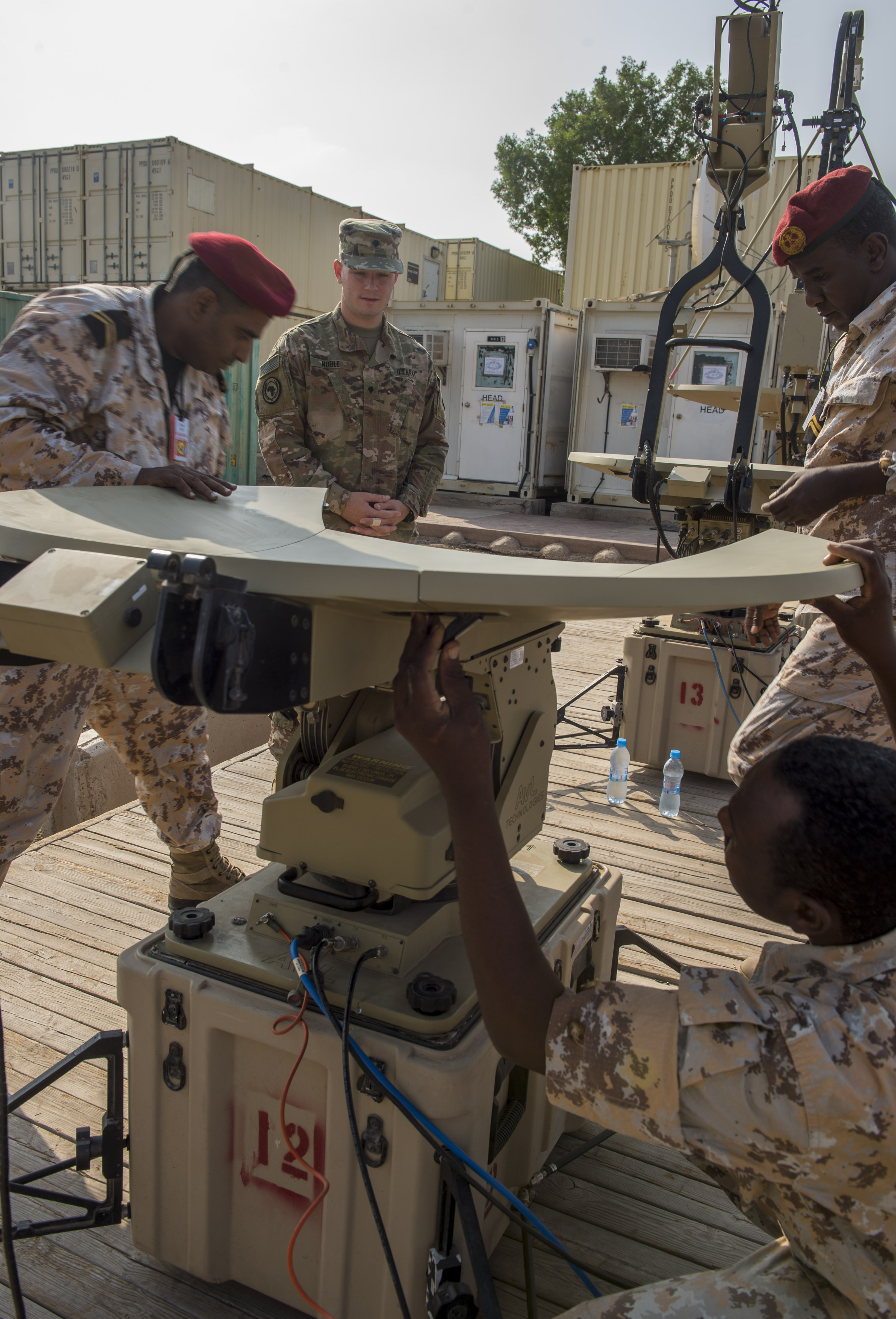 U.S. Army Spc. Taylor Noble, a multisystem transmission operator and maintainer assigned to the Combined Joint Task Force - Horn of Africa (CJTF-HOA) Communications Directorate, watches as service members of the Djibouti Armed Forces (FAD) set up an antenna during a military-to-military exchange course at Camp Lemonnier, Djibouti, Jan. 8, 2018. Throughout a two-week period, communications experts advised Djiboutian service members on how to set up, operate, maintain, and troubleshoot network equipment to increase communication capabilities between African Union Mission in Somalia forces. (U.S. Air Force photo illustration by Staff Sgt. Timothy Moore)