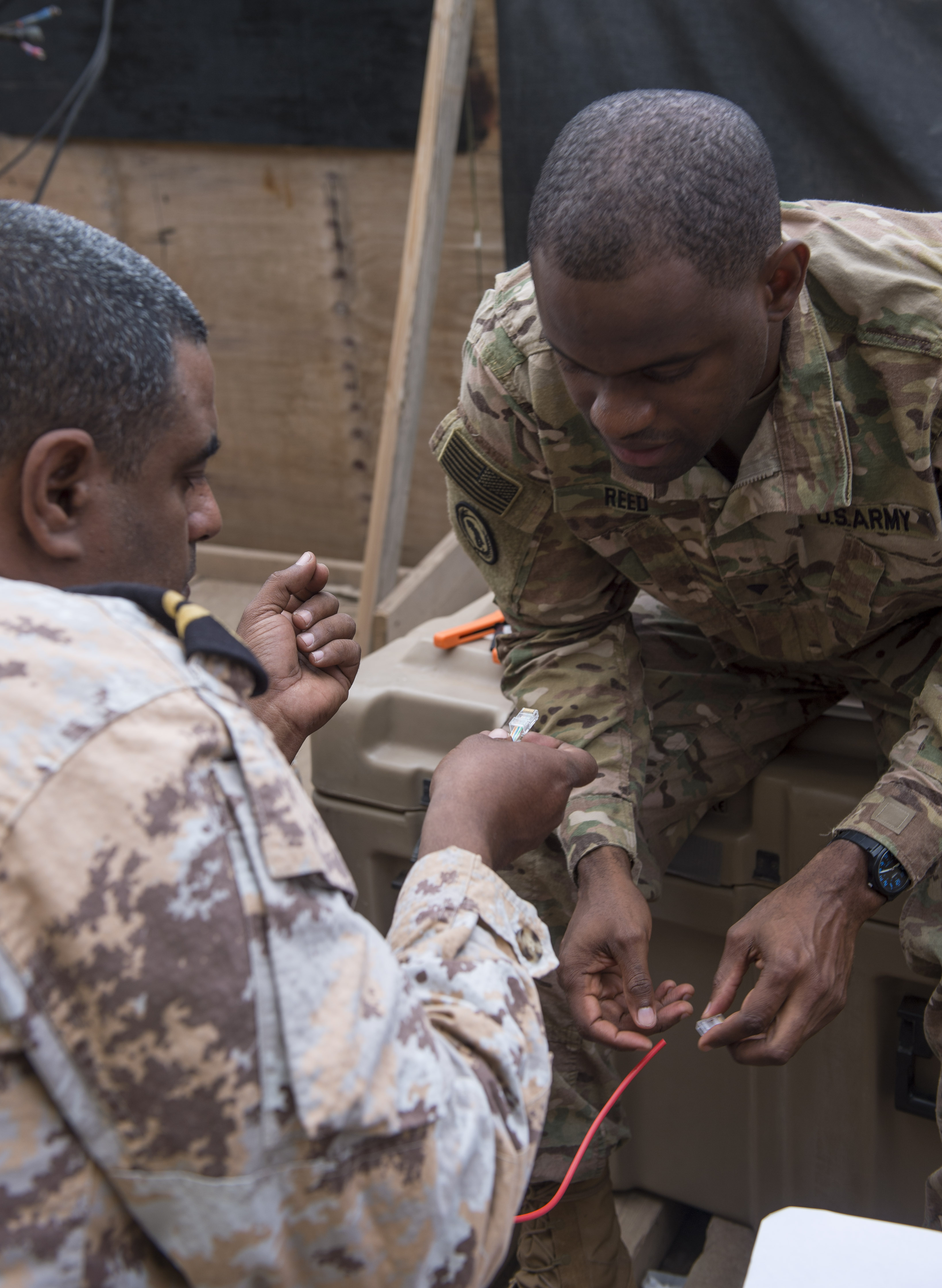 U.S. Army Spc. William Reed, a multisystem transmission operator and maintainer assigned to the Combined Joint Task Force - Horn of Africa (CJTF-HOA) Communications Directorate, inspects the cable connector created by a Djibouti Armed Forces member during a military-to-military exchange course at Camp Lemonnier, Djibouti, Jan. 10, 2018. Throughout a two-week period, communications experts advised Djiboutian service members on how to set up, operate, maintain, and troubleshoot network equipment to increase communication capabilities between African Union Mission in Somalia forces. (U.S. Air Force photo by Staff Sgt. Timothy Moore)
