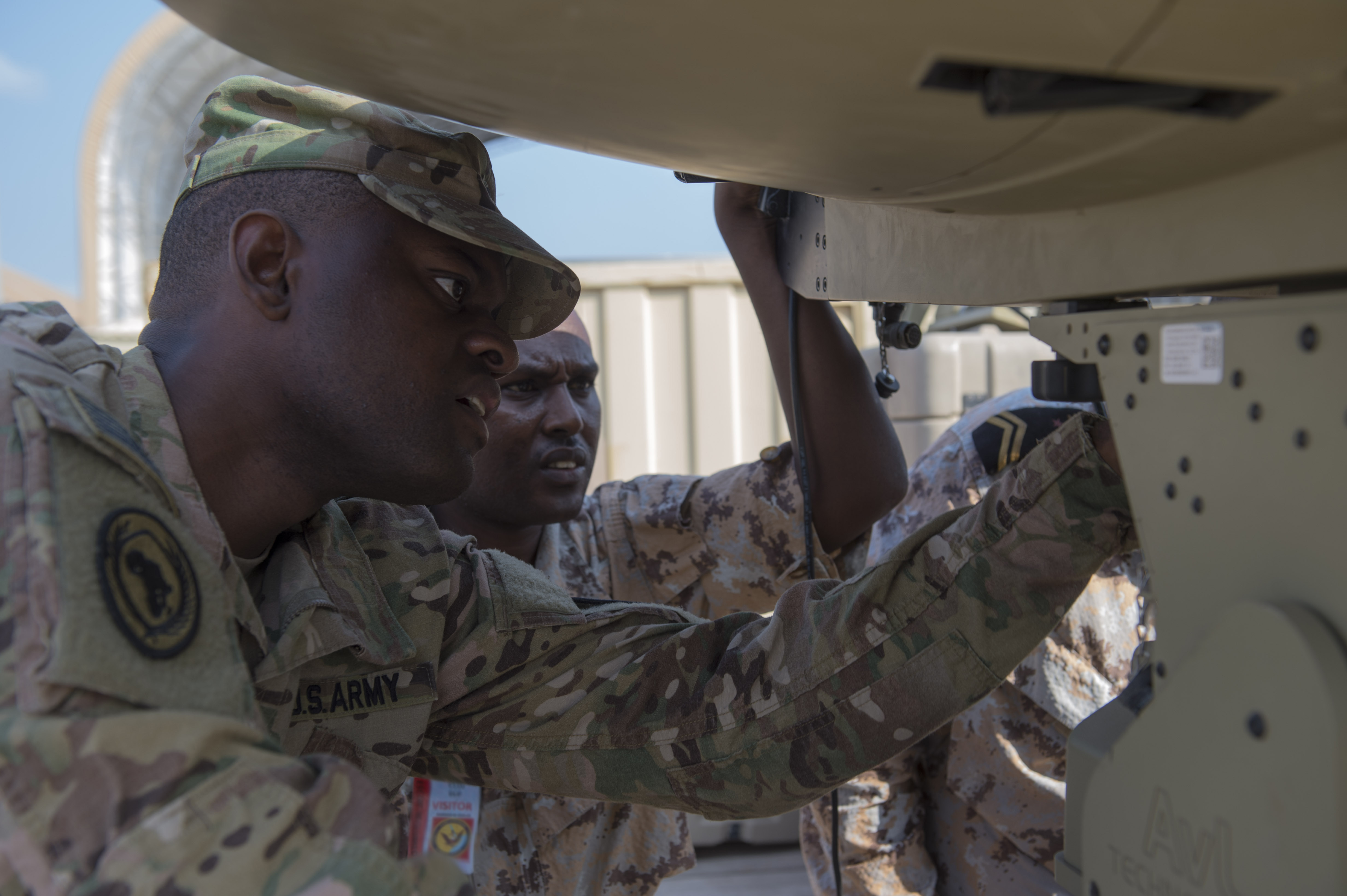 U.S. Army Spc. William Reed, a multisystem transmission operator and maintainer assigned to the Combined Joint Task Force - Horn of Africa (CJTF-HOA) Communications Directorate, helps a service member of the Djibouti Armed Forces (FAD) set up an antenna during a military-to-military exchange course at Camp Lemonnier, Djibouti, Jan. 8, 2018. Throughout a two-week period, communications experts advised Djiboutian service members on how to set up, operate, maintain, and troubleshoot network equipment to increase communication capabilities between African Union Mission in Somalia forces. (U.S. Air Force photo illustration by Staff Sgt. Timothy Moore)