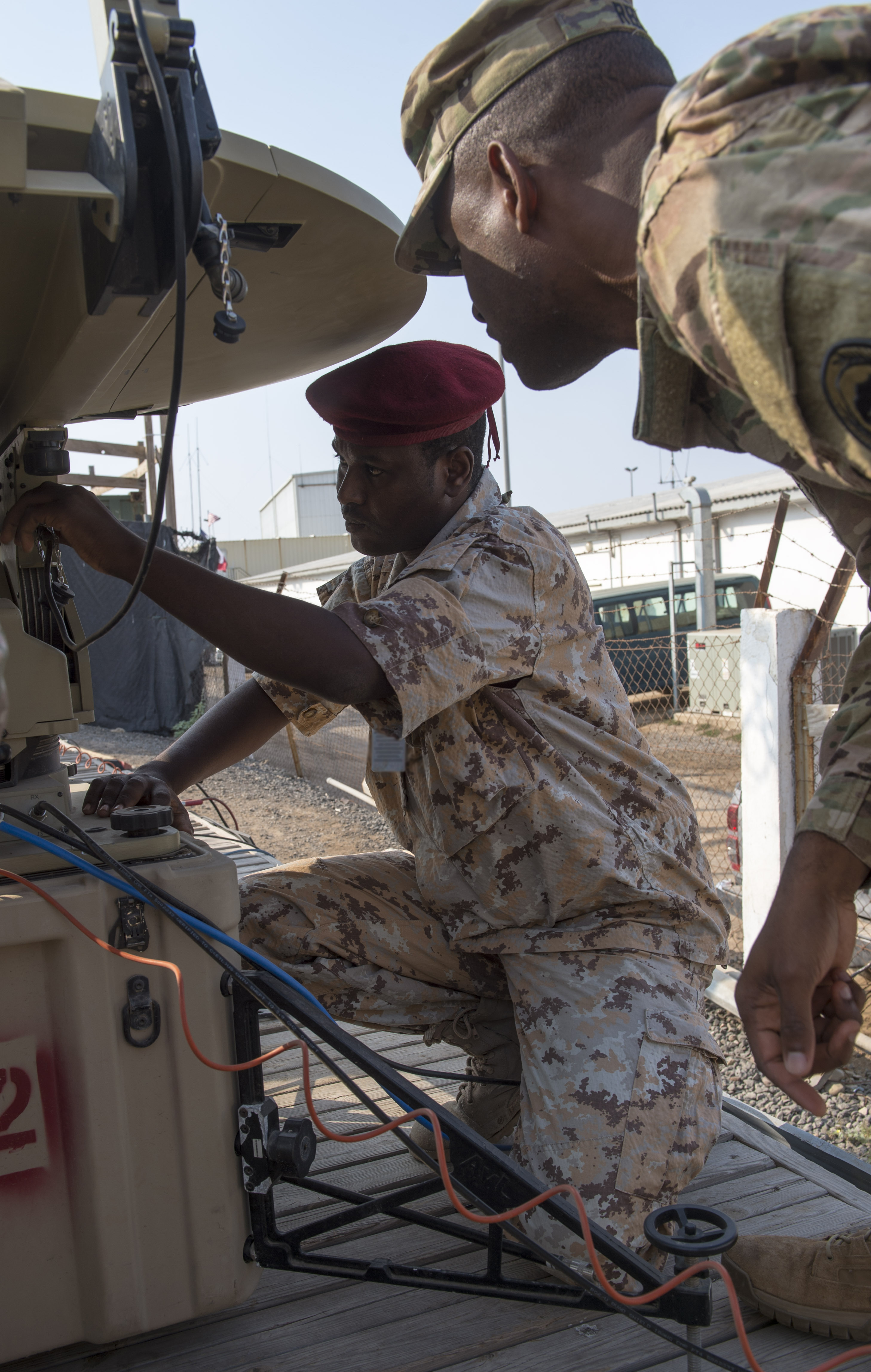 U.S. Army Spc. William Reed, a multisystem transmission operator and maintainer assigned to the Combined Joint Task Force - Horn of Africa (CJTF-HOA) Communications Directorate, watches as a service member of the Djibouti Armed Forces (FAD) sets up an antenna during a military-to-military exchange course at Camp Lemonnier, Djibouti, Jan. 8, 2018. Throughout a two-week period, communications experts advised Djiboutian service members on how to set up, operate, maintain, and troubleshoot network equipment to increase communication capabilities between African Union Mission in Somalia forces. (U.S. Air Force photo illustration by Staff Sgt. Timothy Moore)