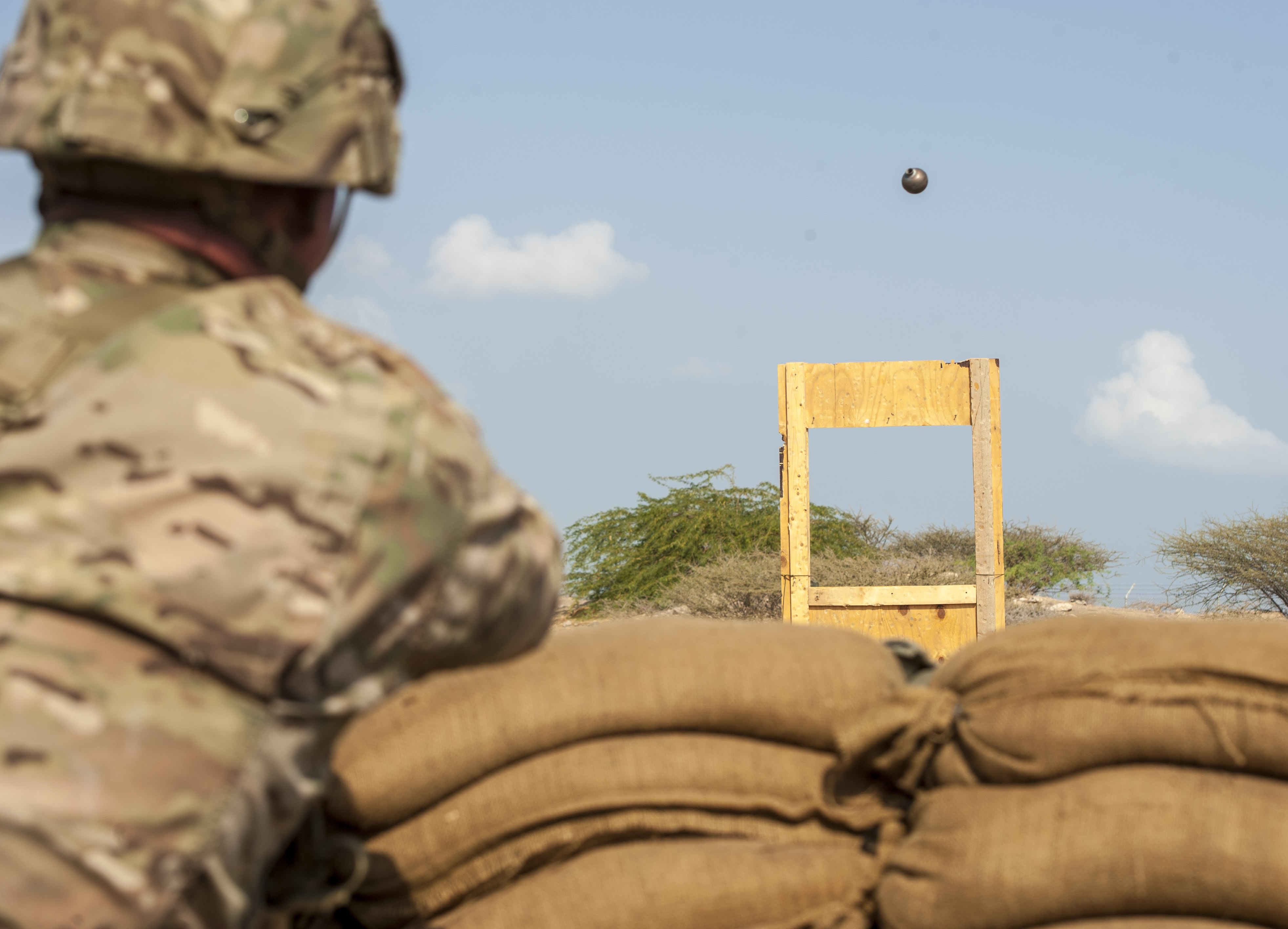 A U.S. Army Soldier assigned to Combined Joint Task Force - Horn of Africa throws a training grenade through a window in preparation for an Expert Infantryman Badge (EIB) evaluation at Camp Lemonnier, Djibouti, Jan. 23, 2018. The EIB is a coveted special skills badge that requires infantry Soldiers to pass a five-day evaluation that consists of an Army Physical Fitness Test, day and night land navigation, a 12-mile forced march, and 30 individual tasks covering weapons, medical, and security patrol skills. In an April 2016 EIB iteration at Camp Lemonnier, only 15 percent of candidates earned the badge. (U.S. Air Force photo by Staff Sgt. Timothy Moore)
