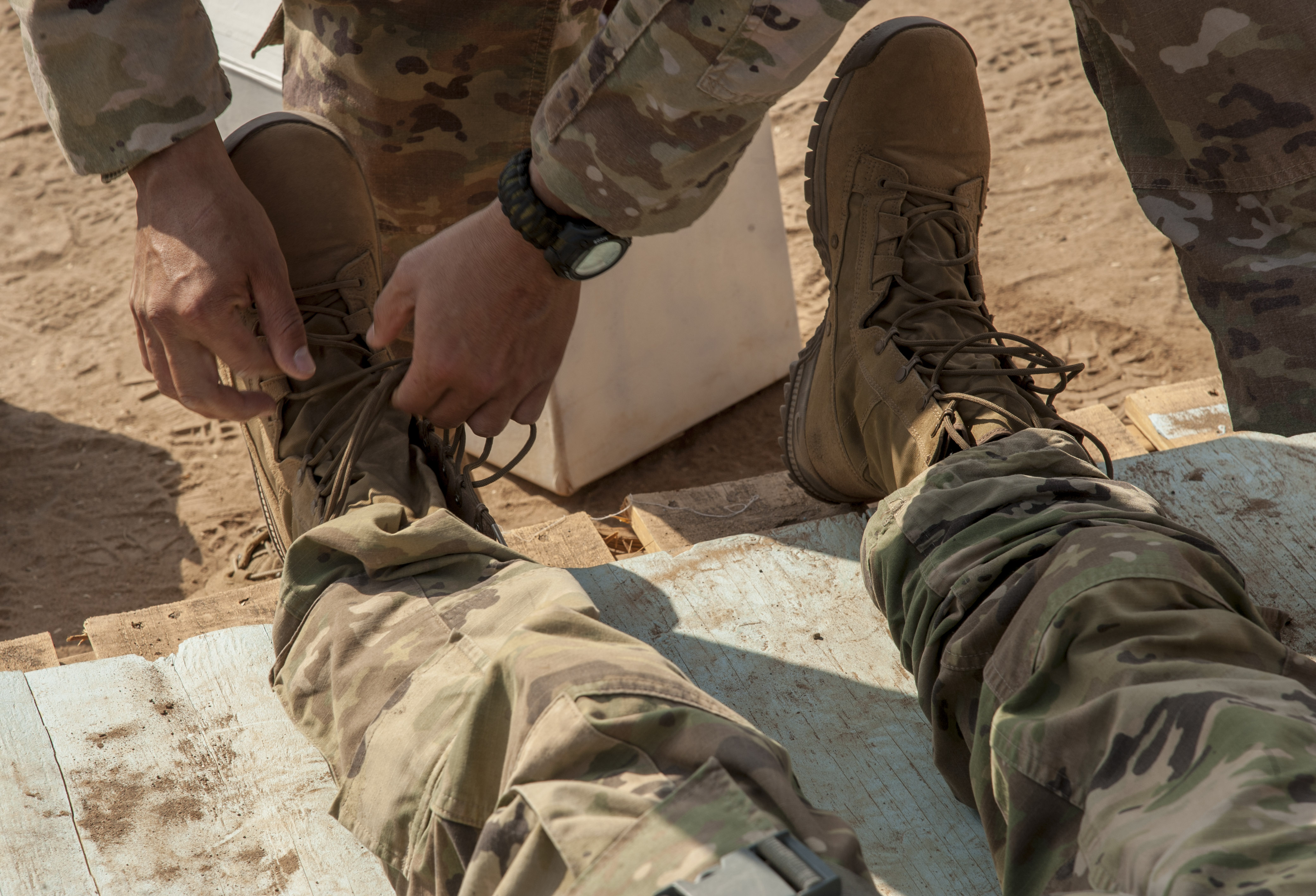 A U.S. Army Soldier assigned to Combined Joint Task Force - Horn of Africa loosens the boots of a simulated heat casualty during training for an Expert Infantryman Badge (EIB) evaluation at Camp Lemonnier, Djibouti, Jan. 23, 2018. The EIB is a coveted special skills badge that requires infantry Soldiers to pass a five-day evaluation that consists of an Army Physical Fitness Test, day and night land navigation, a 12-mile forced march, and 30 individual tasks covering weapons, medical, and security patrol skills. In an April 2016 EIB iteration at Camp Lemonnier, only 15 percent of candidates earned the badge. (U.S. Air Force photo by Staff Sgt. Timothy Moore)