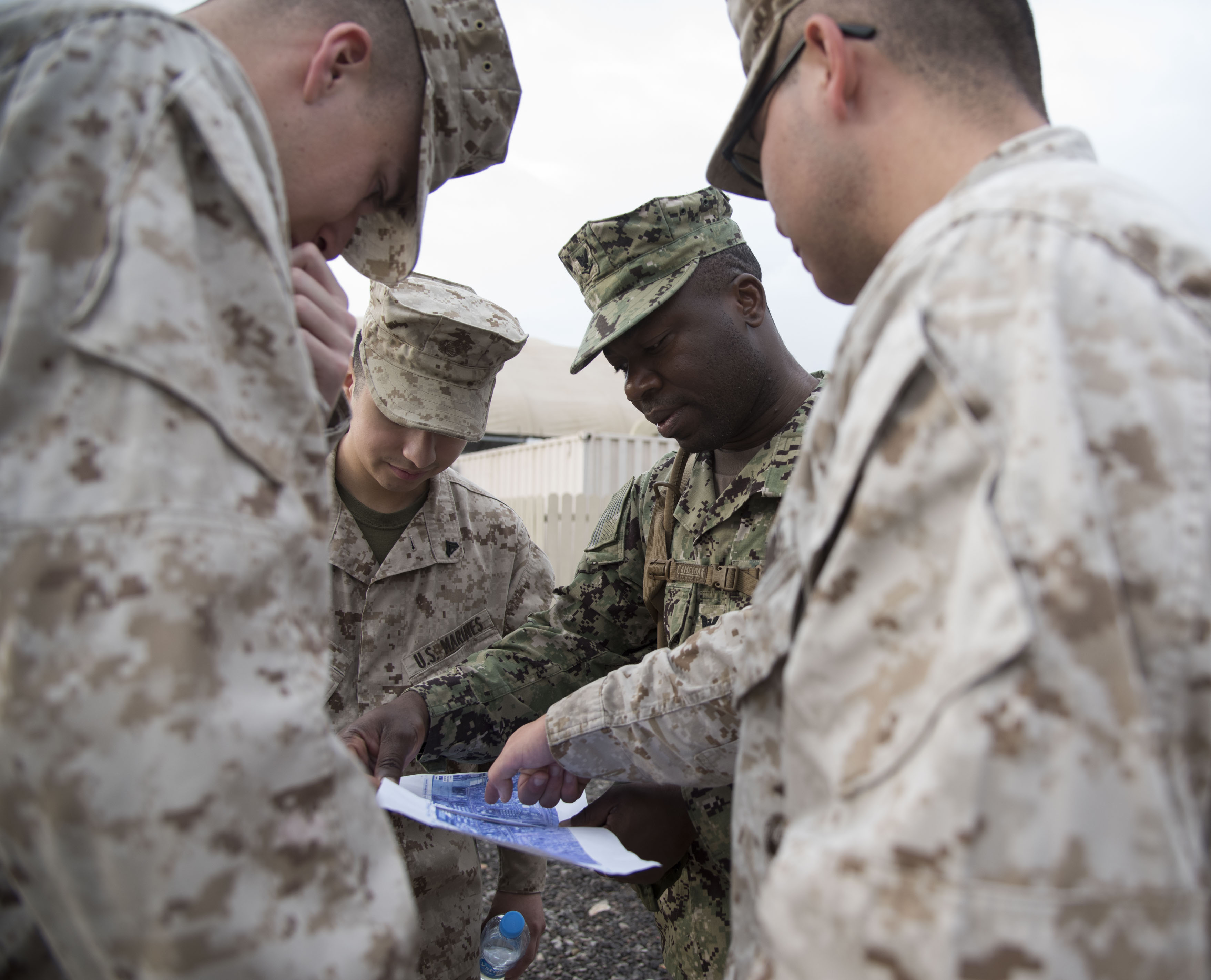 U.S. service members look over a map as part of land navigation training during a Joint Corporals Course hosted by Combined Joint Task Force – Horn of Africa at Camp Lemonnier, Jan. 11, 2018. The Joint Corporals Course is designed to provide junior service members with the knowledge and skills necessary to assume leadership roles of greater responsibility as a non-commissioned officer, as well as strengthen bonds between participating militaries. (U.S. Air National Guard photo by Staff Sgt. Allyson L. Manners)