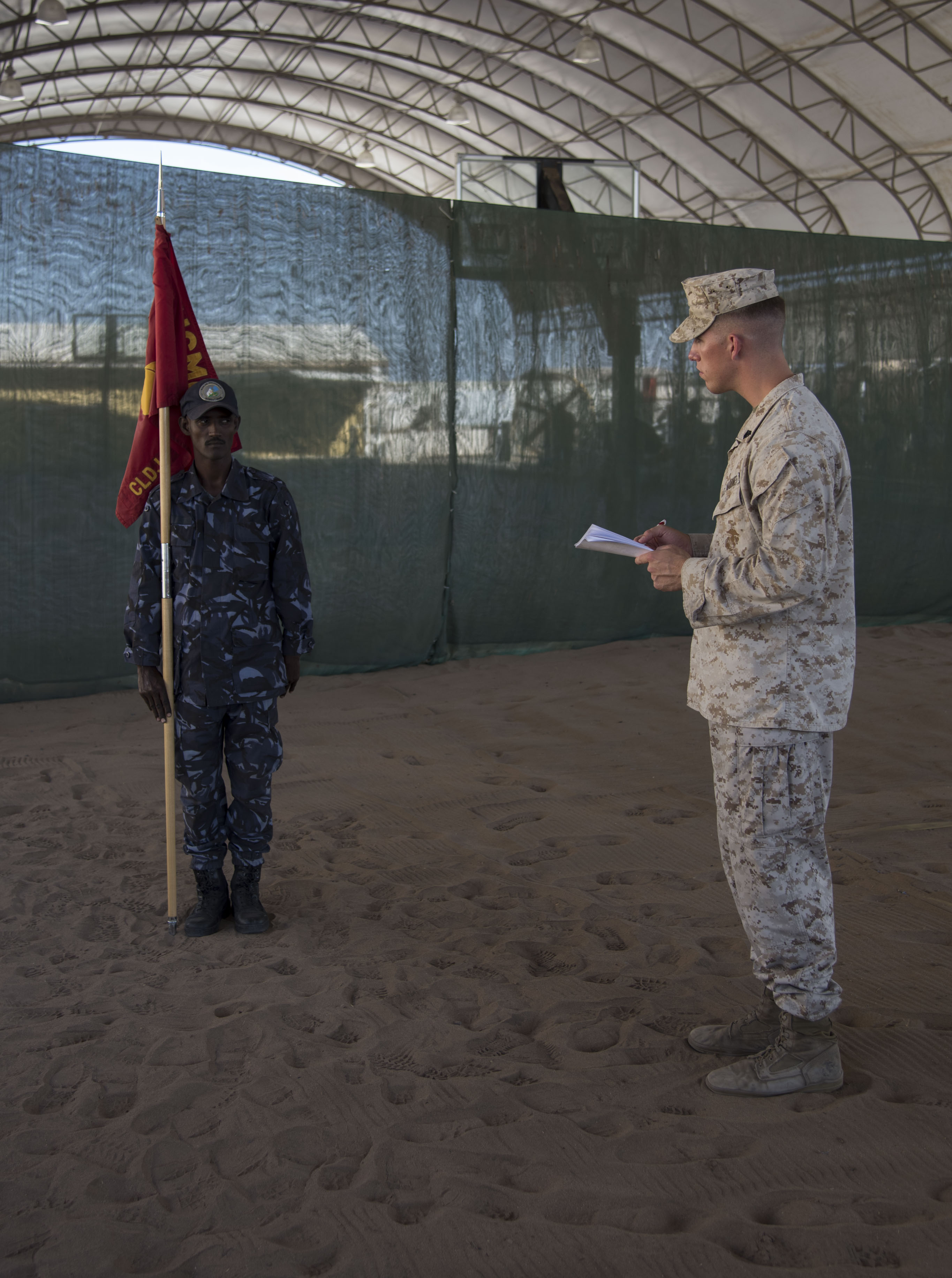 U.S. Marine Corps Sgt. Jacob Blanzy examines a Djiboutian Coast Guard member on during a sword and guidon evaluation as part of a Joint Corporals Course hosted by Combined Joint Task Force – Horn of Africa at Camp Lemonnier, Jan. 17, 2018. The Joint Corporals Course is designed to provide junior service members with the knowledge and skills necessary to assume leadership roles of greater responsibility as a non-commissioned officer, as well as strengthen bonds between participating militaries. (U.S. Air National Guard photo by Staff Sgt. Allyson L. Manners)
