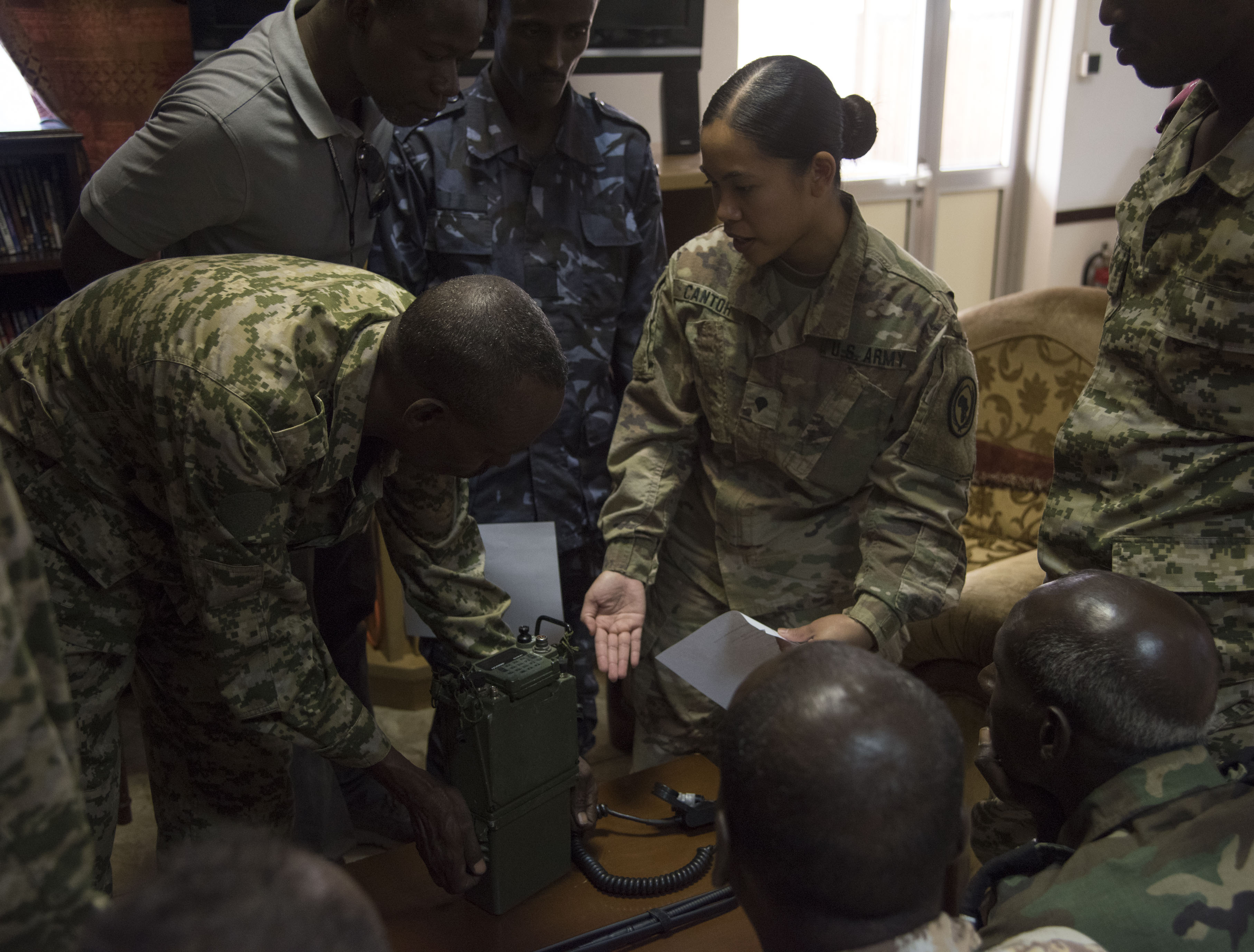 U.S. Army Spc. Christinejoy Cantor instructs Djiboutian military members on radio usage during a Tactical Communications class as part of a Joint Corporals Course hosted by Combined Joint Task Force – Horn of Africa at Camp Lemonnier, Jan. 11, 2018. The Joint Corporals Course is designed to provide junior service members with the knowledge and skills necessary to assume leadership roles of greater responsibility as a non-commissioned officer, as well as strengthen bonds between participating militaries. (U.S. Air National Guard photo by Staff Sgt. Allyson L. Manners)