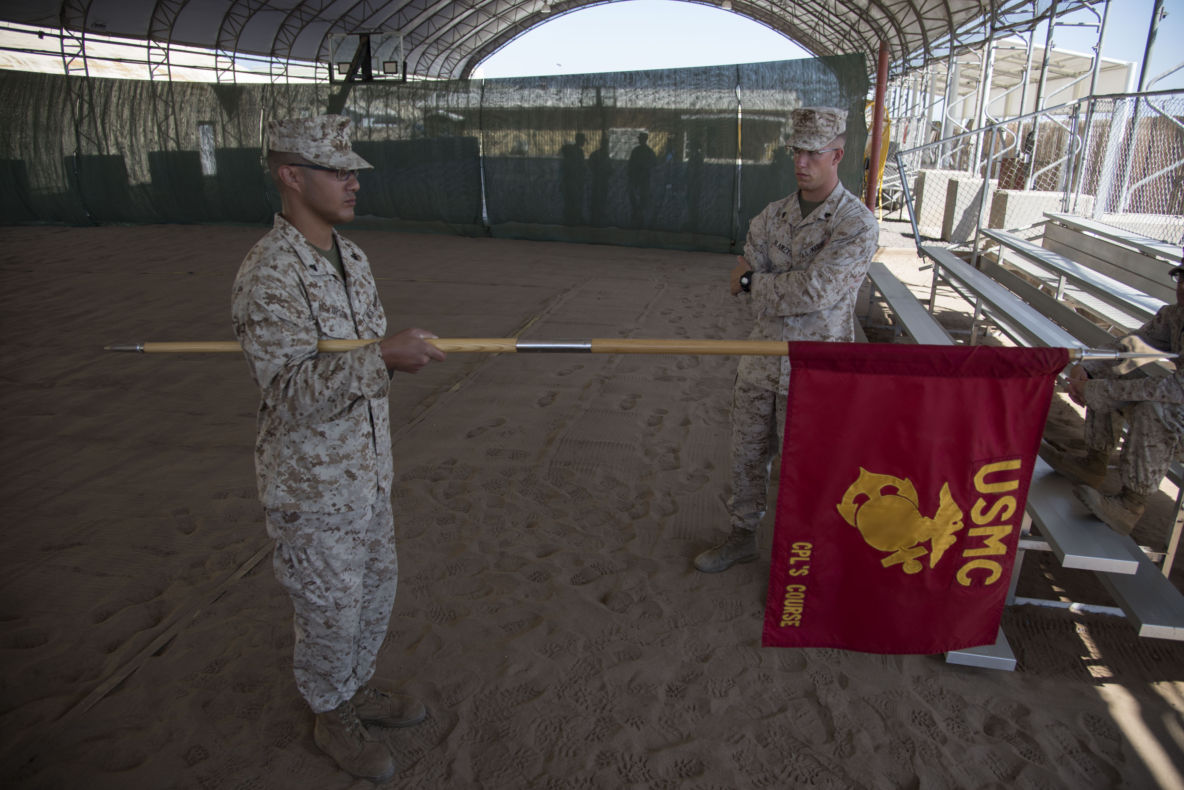 U.S. Marine Corps Sgt. Jacob Blanzy examines Cpl. Devin Upson during a sword and guidon evaluation as part of a Joint Corporals Course hosted by Combined Joint Task Force – Horn of Africa at Camp Lemonnier, Jan. 17, 2018. The Joint Corporals Course is designed to provide junior service members with the knowledge and skills necessary to assume leadership roles of greater responsibility as a non-commissioned officer, as well as strengthen bonds between participating militaries. (U.S. Air National Guard photo by Staff Sgt. Allyson L. Manners)
