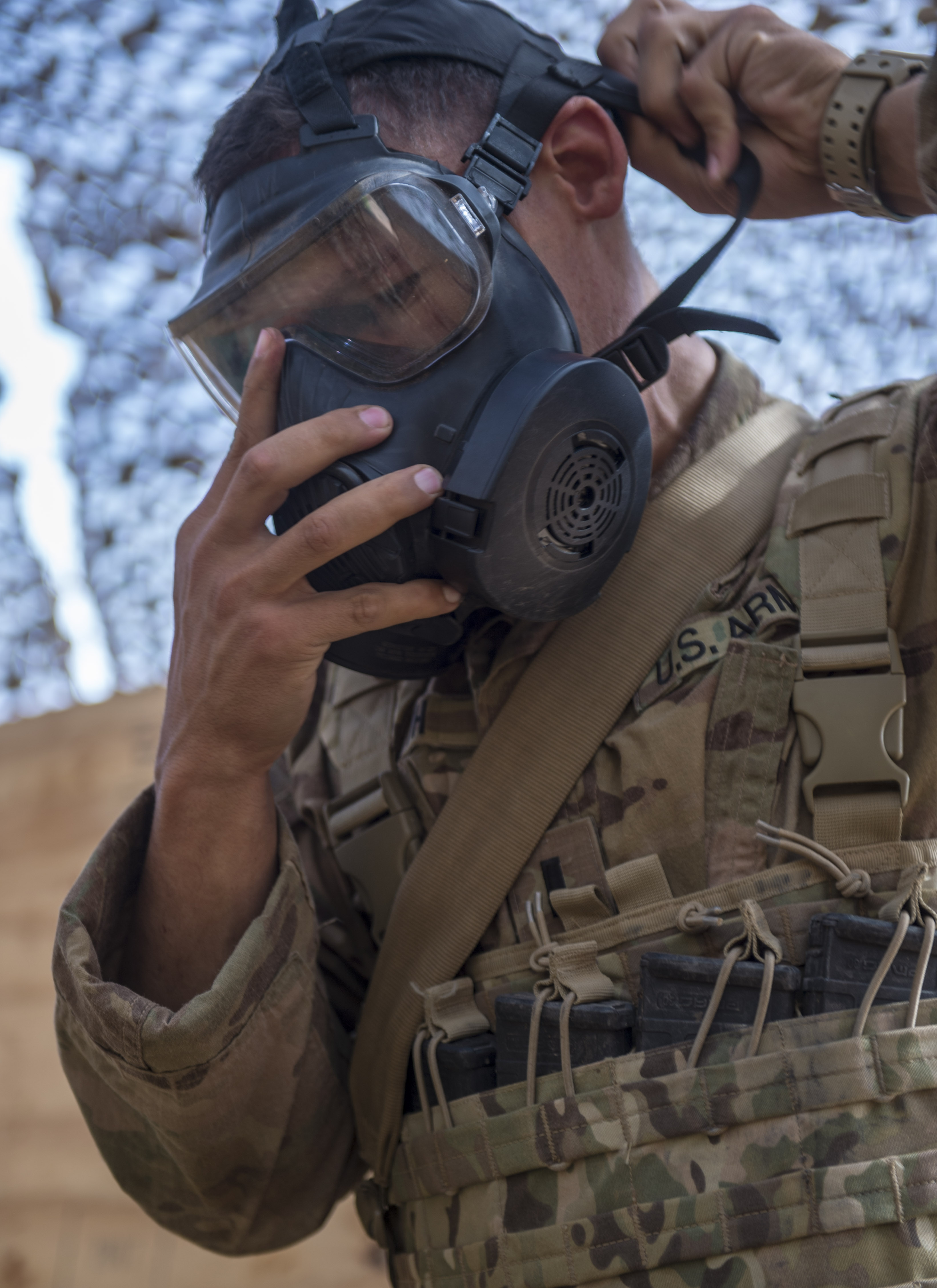 A U.S. Army Soldier assigned to Combined Joint Task Force - Horn of Africa puts on a gas mask during training in preparation for an Expert Infantryman Badge evaluation at Camp Lemonnier, Djibouti, Jan. 24, 2018. After two weeks of training and five days of testing, 50 Soldiers completed the process to earn the coveted special skills badge that requires Soldiers to perform an Army Physical Fitness Test, day and night land navigation, a 12-mile forced march, and 30 individual tasks covering weapons, medical, and security patrol skills. (U.S. Air Force photo by Staff Sgt. Timothy Moore)