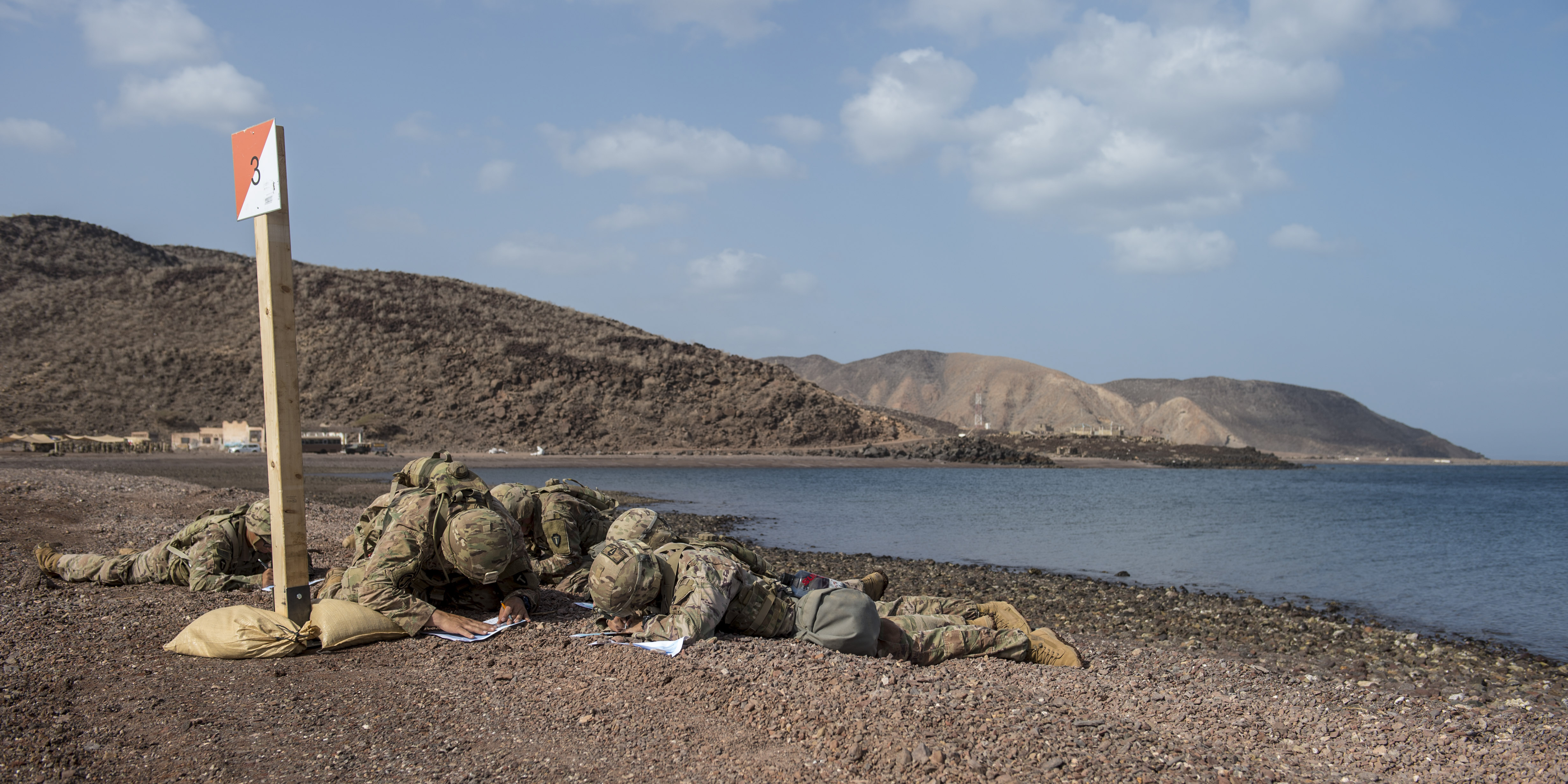 U.S. Army Soldiers assigned to Combined Joint Task Force - Horn of Africa plot grid points during land navigation training in preparation for an Expert Infantryman Badge evaluation at Arta Range, Djibouti, Jan. 25, 2018. After two weeks of training and five days of testing, 50 Soldiers completed the process to earn the coveted special skills badge that requires Soldiers to perform an Army Physical Fitness Test, day and night land navigation, a 12-mile forced march, and 30 individual tasks covering weapons, medical, and security patrol skills. (U.S. Air Force photo by Staff Sgt. Timothy Moore)