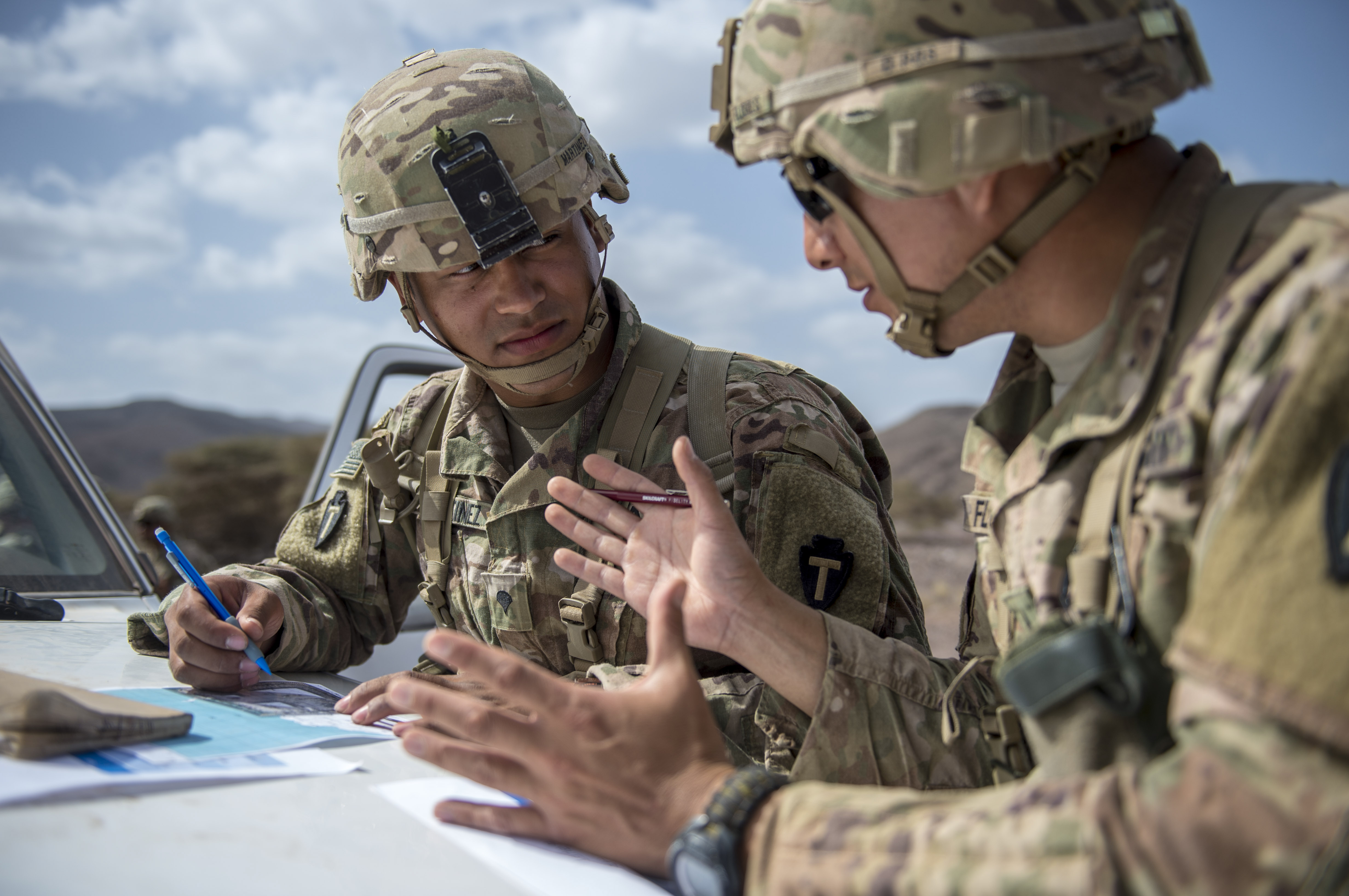 U.S. Army Soldiers assigned to Combined Joint Task Force - Horn of Africa discuss land navigation during training in preparation for an Expert Infantryman Badge evaluation at Arta Range, Djibouti, Jan. 25, 2018. After two weeks of training and five days of testing, 50 Soldiers completed the process to earn the coveted special skills badge that requires Soldiers to perform an Army Physical Fitness Test, day and night land navigation, a 12-mile forced march, and 30 individual tasks covering weapons, medical, and security patrol skills.  (U.S. Air Force photo by Staff Sgt. Timothy Moore)