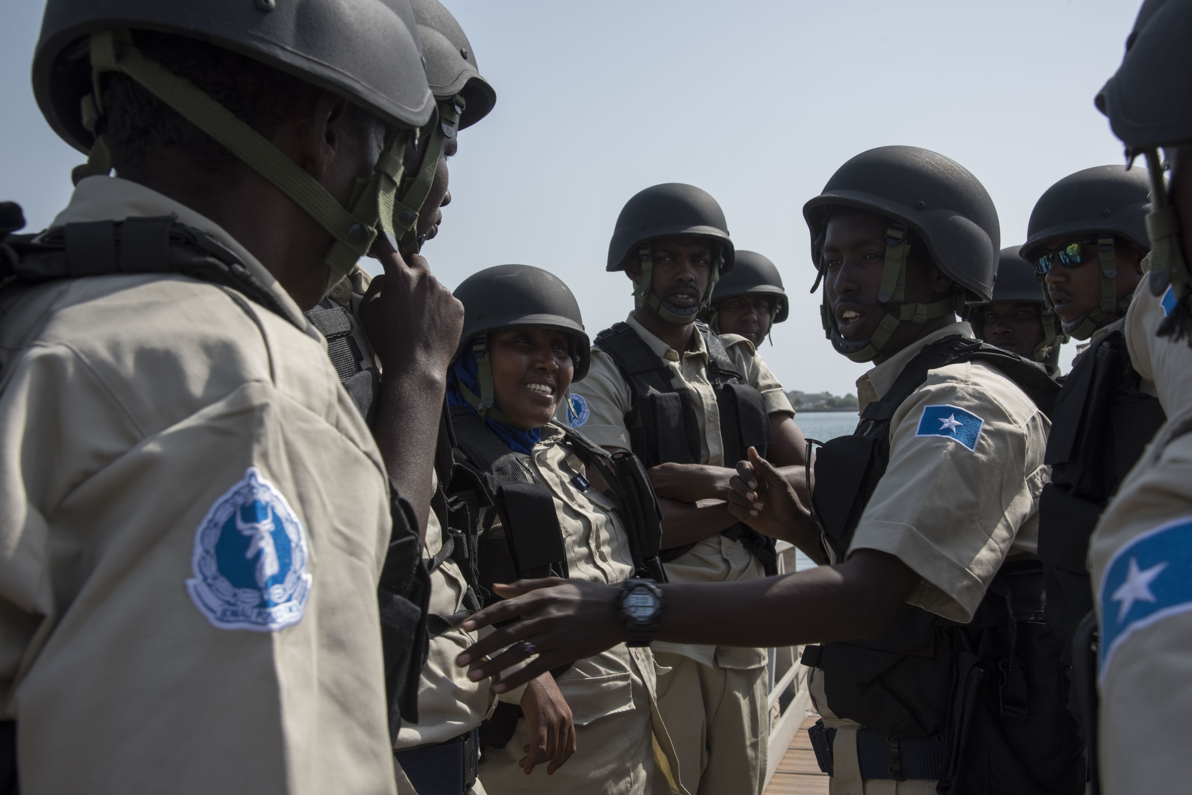 Somali maritime police talk together before running through a visit, board, search and seizure drill (VBSS) during exercise Cutlass Express 2018 in the Port of Djibouti Feb. 5, 2018. Cutlass Express is designed to improve cooperation, maritime domain awareness and information sharing practices to increase capabilities between the U.S., East African and Western Indian Ocean nations. (U.S. Air National Guard photo by Staff Sgt. Allyson Manners)
