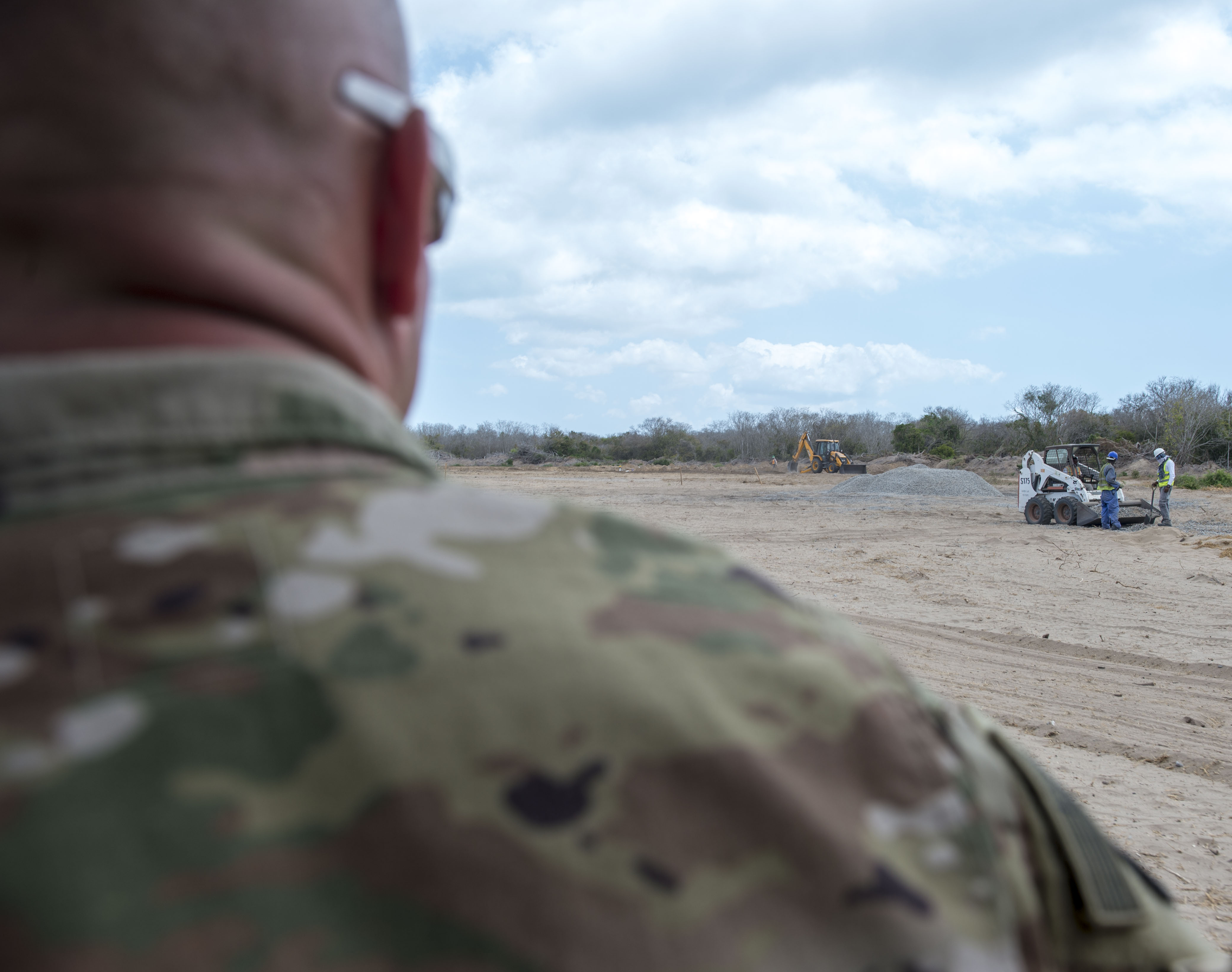 U.S. Army Lt. Col. Todd Martin, safety officer assigned to the Combined Joint Task Force - Horn of Africa (CJTF-HOA) Safety directorate, watches local national workers during a battlefield circulation site visit at Camp Simba in Manda Bay, Kenya, Feb. 24, 2018. The CJTF-HOA Safety and Inspector General directorates provide support to the service members, Department of Defense civilians, and local national and third-country national contractors who work on the camp. Though many of the members at the camp don't fall under CJTF-HOA, many of the concerns that affect the CJTF-HOA personnel also affect them and vice versa. (U.S. Air Force photo by Staff Sgt. Timothy Moore)