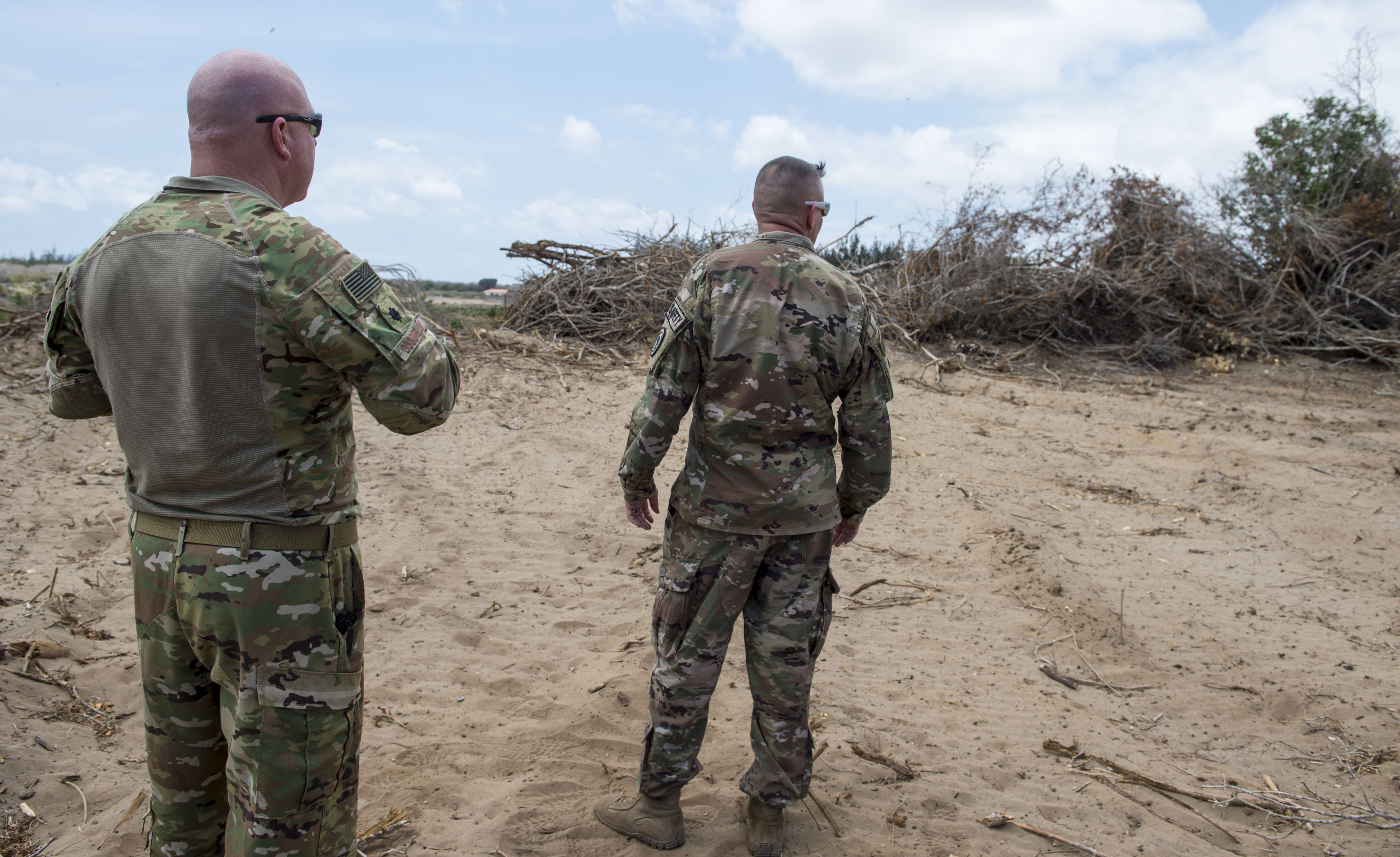 U.S. Air Force Lt. Col. Vance Goodfellow, left, 475th Expeditionary Air Base Squadron (EABS) commander, and U.S. Army Lt. Col. Todd Martin, safety officer assigned to the Combined Joint Task Force - Horn of Africa (CJTF-HOA) Safety directorate, look at trees that are being cleared during a battlefield circulation site visit at Camp Simba in Manda Bay, Kenya, Feb. 24, 2018. Camp Simba is currently operated by the 475th EABS, who fall under the 435th Air Expeditionary Wing, but the property hosts CJTF-HOA personnel and is in the CJTF-HOA area of operations. As such, the CJTF-HOA Safety and Inspector General offices provide support to the service members, Department of Defense civilians, and local national contractors who work on the camp. (U.S. Air Force photo by Staff Sgt. Timothy Moore)