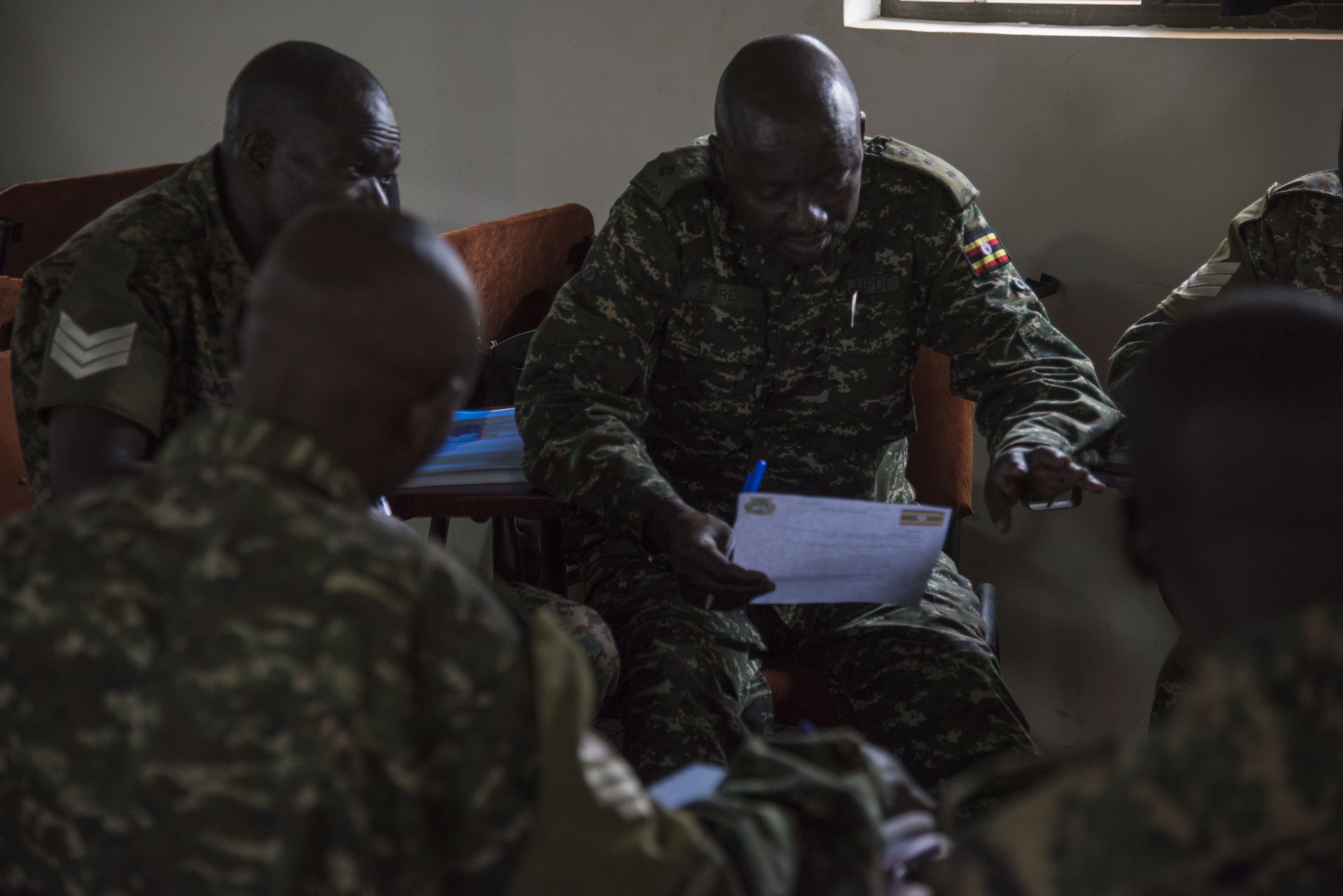 A Uganda People's Defence Force (UPDF) soldier discusses notes with his group during a Civil Affairs (CA) Tactical Company Course, hosted by the 407th Civil Affairs (CA) Battalion, attached to the Combined Joint Task Force - Horn of Africa, at Camp Singo, Uganda, Feb. 08, 2018. CJTF-HOA service members are forward deployed to Camp Singo to advise and assist the UPDF in preparing Ugandan Battle Group 25 for an upcoming deployment in support of the African Union Mission in Somalia (AMISOM). (U.S. Air National Guard photo by Staff Sgt. Allyson L. Manners)