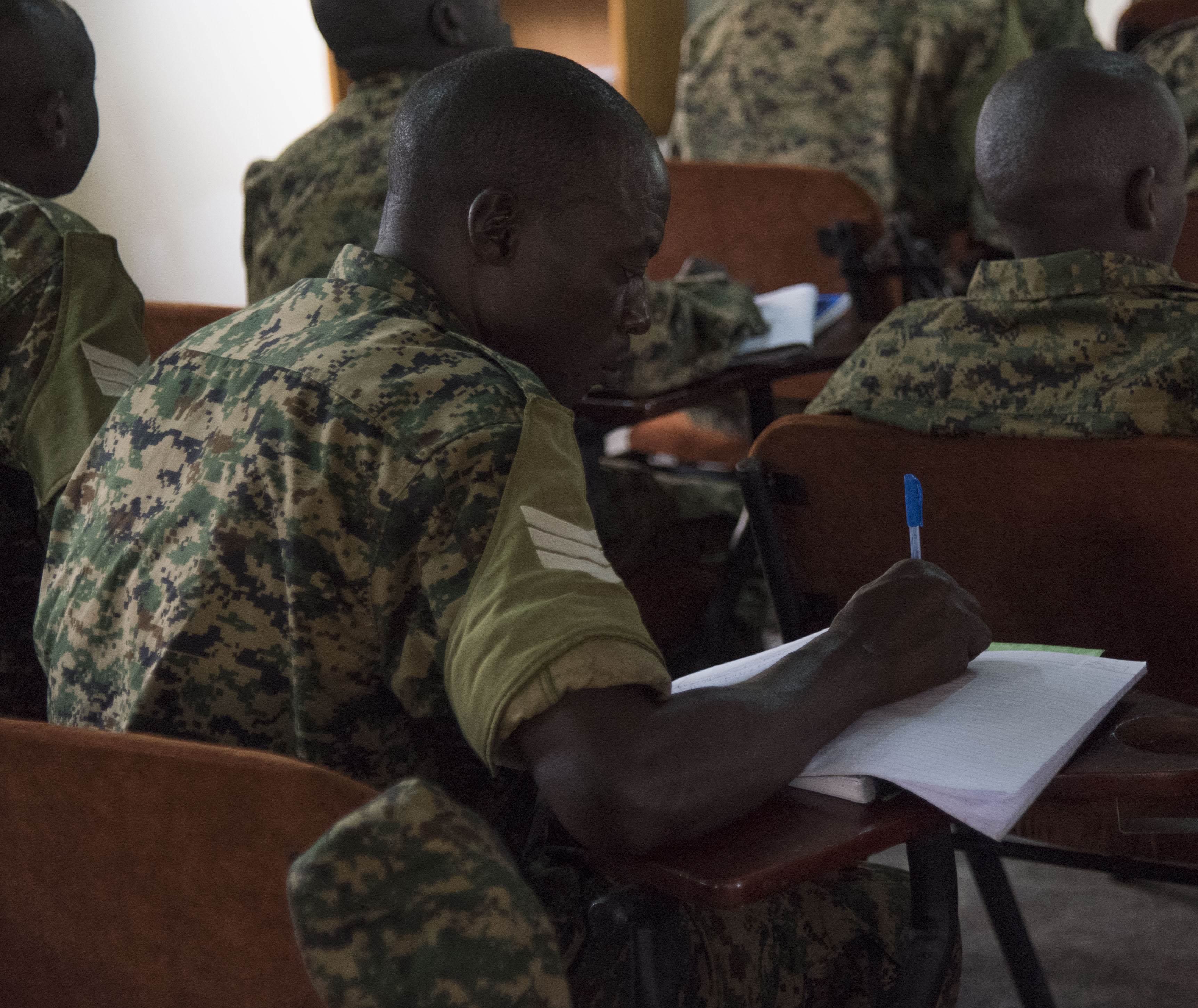 A Uganda People's Defence Force (UPDF) soldier takes notes during a Civil Affairs (CA) Tactical Company Course, hosted by the 407th Civil Affairs (CA) Battalion, attached to the Combined Joint Task Force - Horn of Africa, at Camp Singo, Uganda, Feb. 08, 2018. CJTF-HOA service members are forward deployed to Camp Singo to advise and assist the UPDF in preparing Ugandan Battle Group 25 for an upcoming deployment in support of the African Union Mission in Somalia (AMISOM). (U.S. Air National Guard photo by Staff Sgt. Allyson L. Manners)