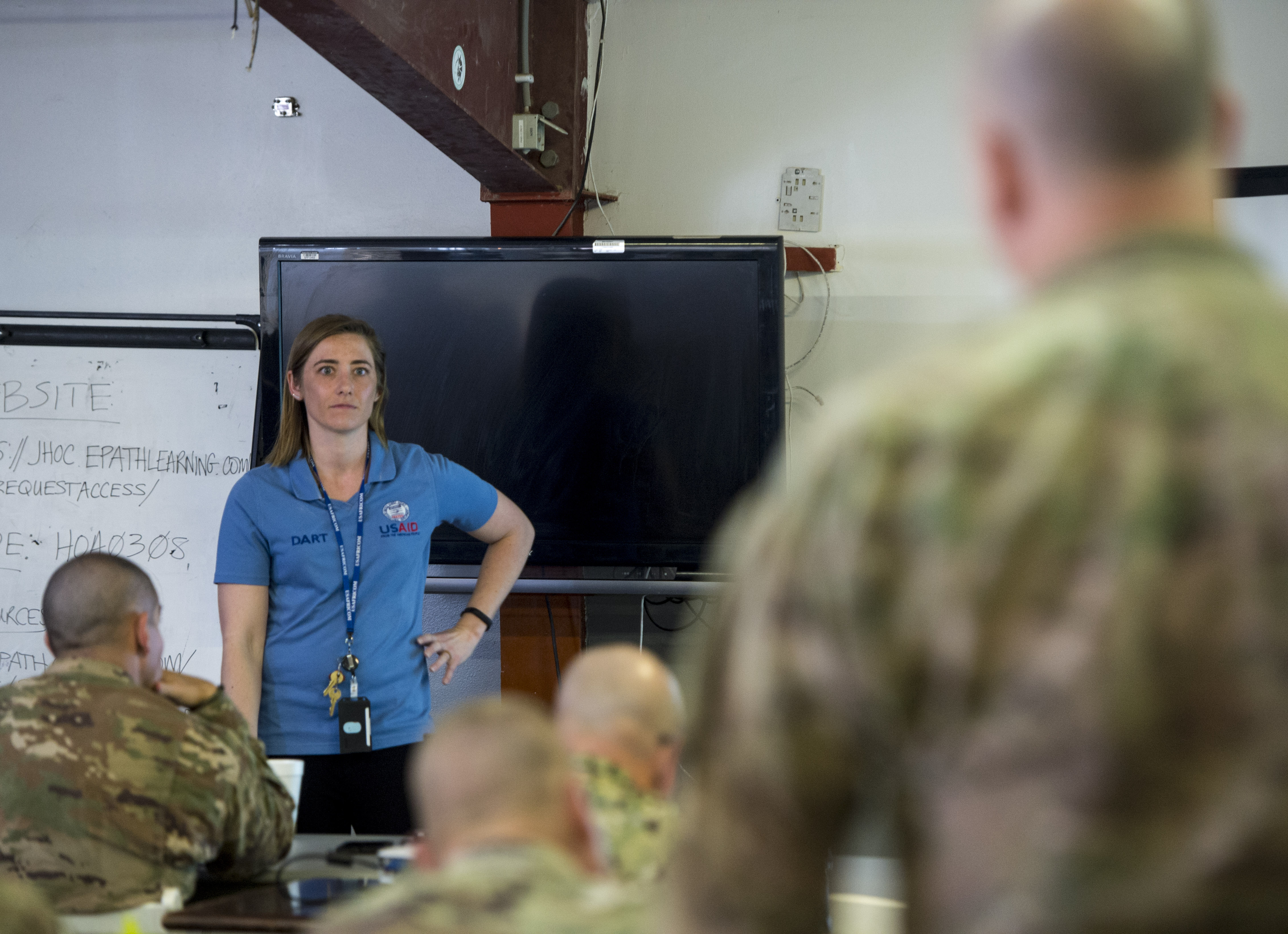 KJ Pettersen, an instructor with the U.S. Agency for International Development's Office of Foreign Disaster Assistance, listens as a service member assigned to Combined Joint Task Force - Horn of Africa briefs a plan for military involvement in a simulated disaster relief operation during a Joint Humanitarian Operations Course at Camp Lemonnier, Djibouti, March 9, 2018. Members attended the second two-day course, which highlighted international disaster response, best practices, and the U.S. military's role when supporting humanitarian assistance and disaster relief operations. (U.S. Air Force photo by Staff Sgt. Timothy Moore)