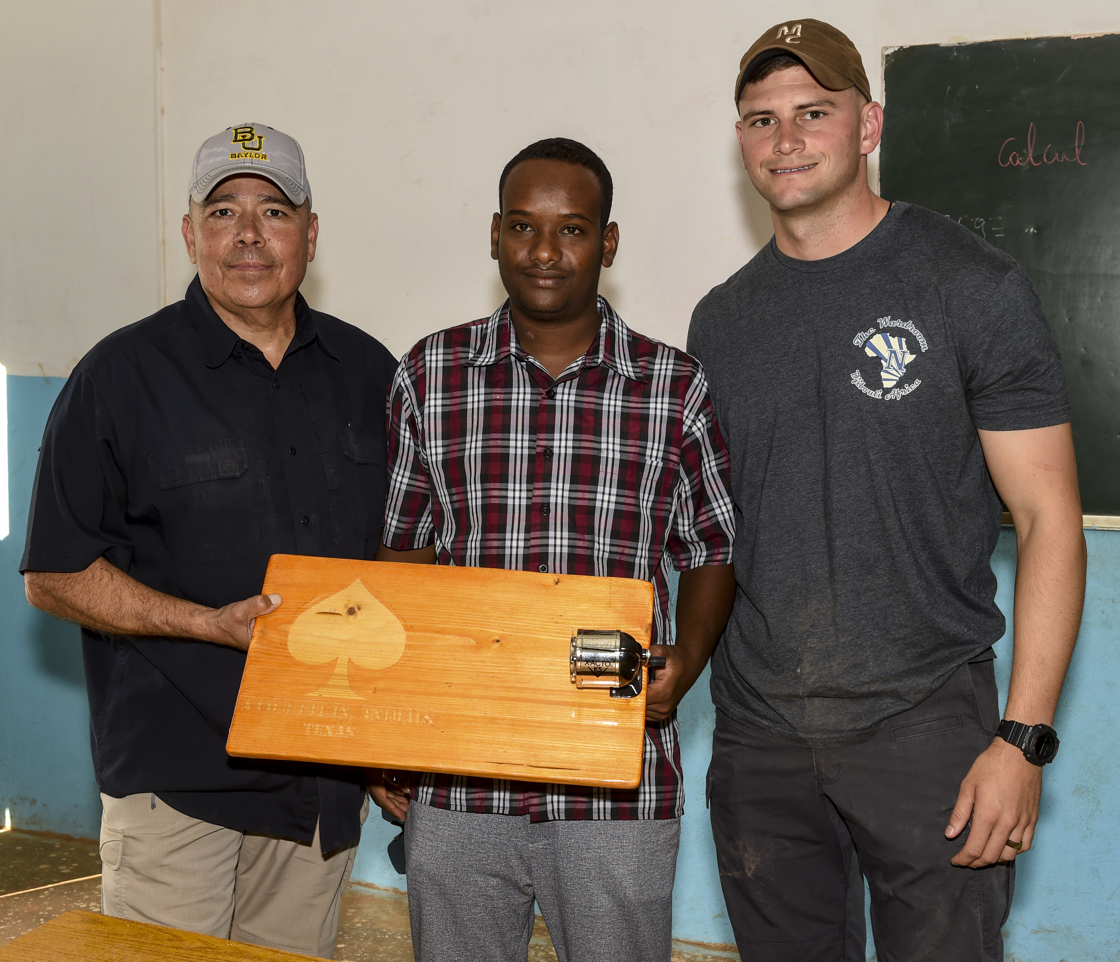 U.S. Army Sgt. 1st Class Juan Vela, left, and 1st Lt. Aidan Dietz, right, both with Animal Company, 3rd Battalion, 141st Infantry Regiment, assigned to Combined Joint Task Force - Horn of Africa (CJTF-HOA), present a portable manual pencil sharpener to Amin Houssein, teacher, in Ali Oune, Djibouti, March 28, 2018. CJTF-HOA service members donated more than $400 of school supplies and sandals to Somali refugee students in Djibouti. (U.S. Air Force photo by Staff Sgt. Timothy Moore)