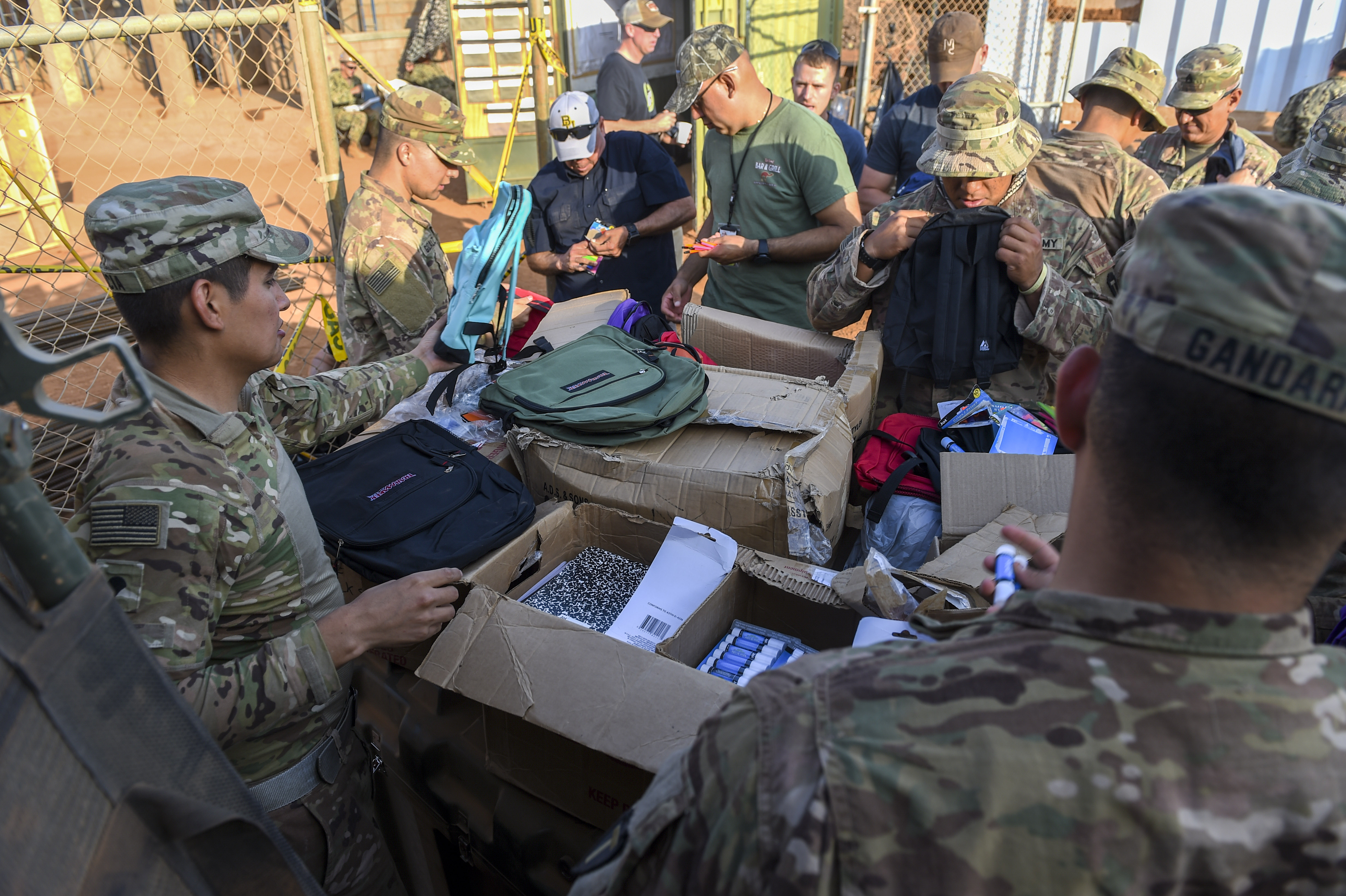 U.S. Army Soldiers with Animal Company, 3rd Battalion, 141st Infantry Regiment, assigned to Combined Joint Task Force - Horn of Africa (CJTF-HOA) put school supplies into backpacks to be given to Somali children in Ali Oune, Djibouti, March 28, 2018. CJTF-HOA service members donated more than $400 of school supplies and sandals to Somali refugees in Djibouti. (U.S. Air Force photo by Staff Sgt. Timothy Moore)