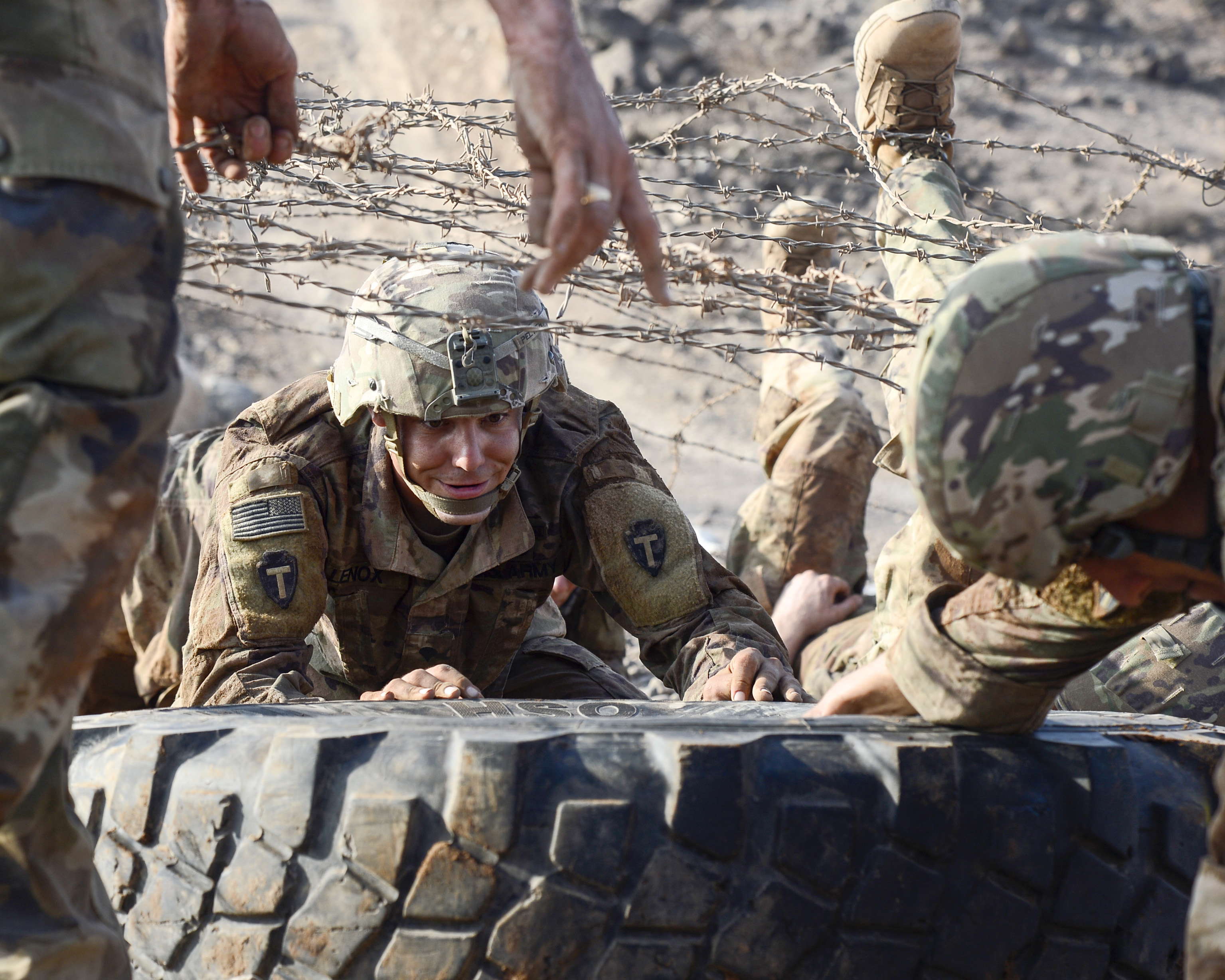 U.S. Army Spc. Aaron Lenox assigned to Alpha Company, 3rd Battalion, 144th Infantry Regiment, Texas Army National Guard assists his team in navigating an obstacle during the French Desert Commando Course at the Centre Dentrainment Au Combat Djibouti in Arta Plage, Djibouti, April 22, 2018.  The four-day phase is the first of two necessary to earn a coveted French Desert Commando Badge. (U.S. Navy Photo by Mass Communication Specialist 2nd Class Timothy M. Ahearn)