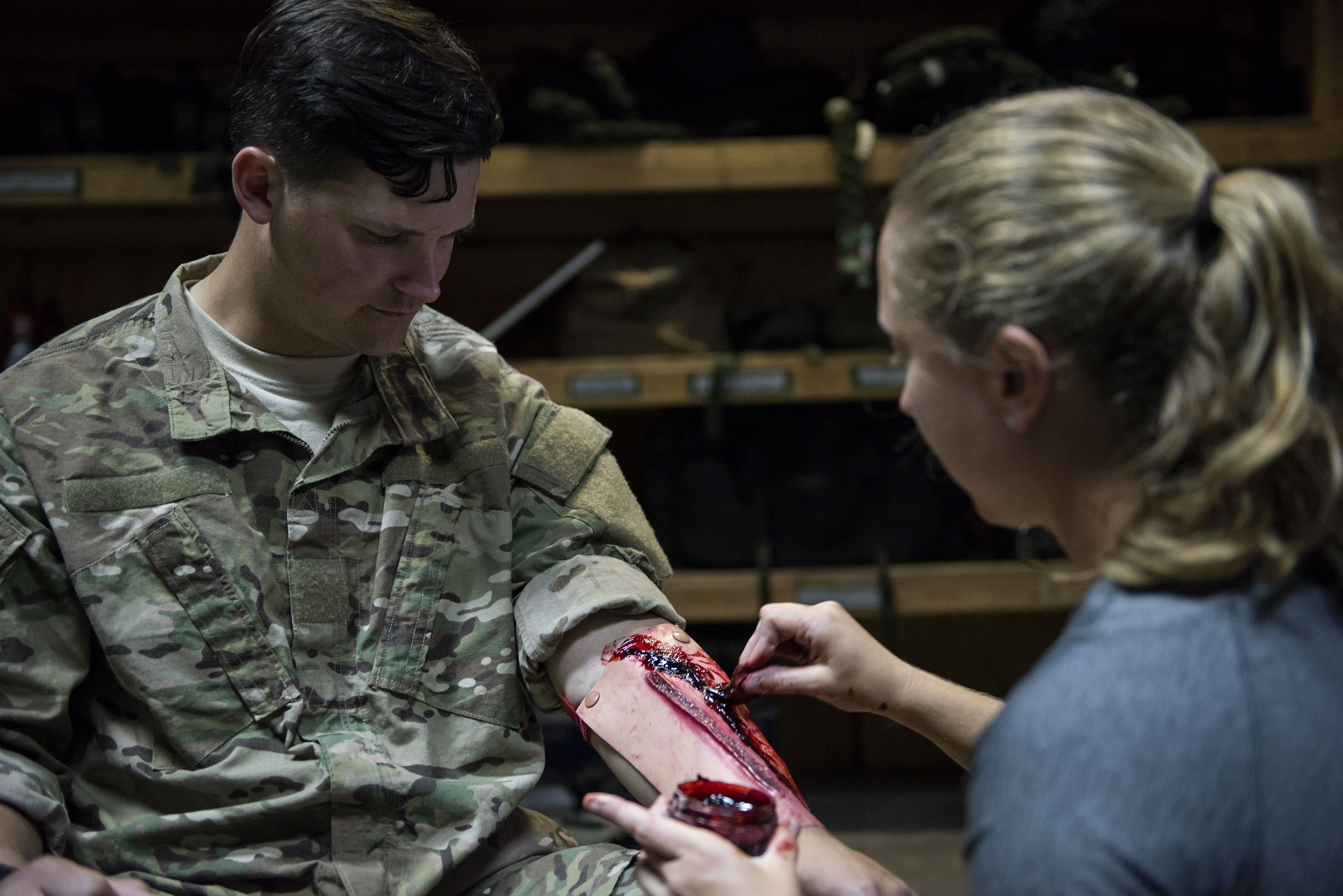 U.S. Air Force Maj. Aspen Terry, a medical officer with the 82nd Expeditionary Rescue Squadron, moulages the arm of Staff Sgt. Alex Stojadinovic, 449th Air Expeditionary Group, on Camp Lemonnier, Djibouti, April 24, 2018. As part of a joint mass casualty training exercise, service members performed various tasks in order to locate, secure and rescue simulated casualties. (U.S. Air National Guard photo by Master Sgt. Sarah Mattison)