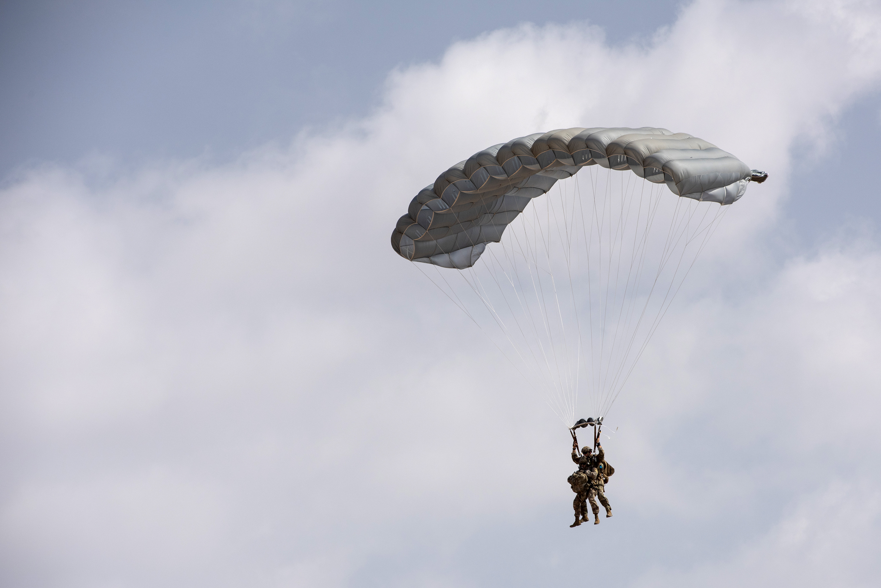 U.S. Air Force Pararescuemen from the 82nd Expeditionary Rescue Squadron participate in a high altitude, low-opening tandem free-fall jump to bring in a medical doctor, in Djibouti City, Djibouti, April 24, 2018. The free-fall jump was conducted as part of a joint training exercise. (U.S. Air National Guard photo by Master Sgt. Sarah Mattison)