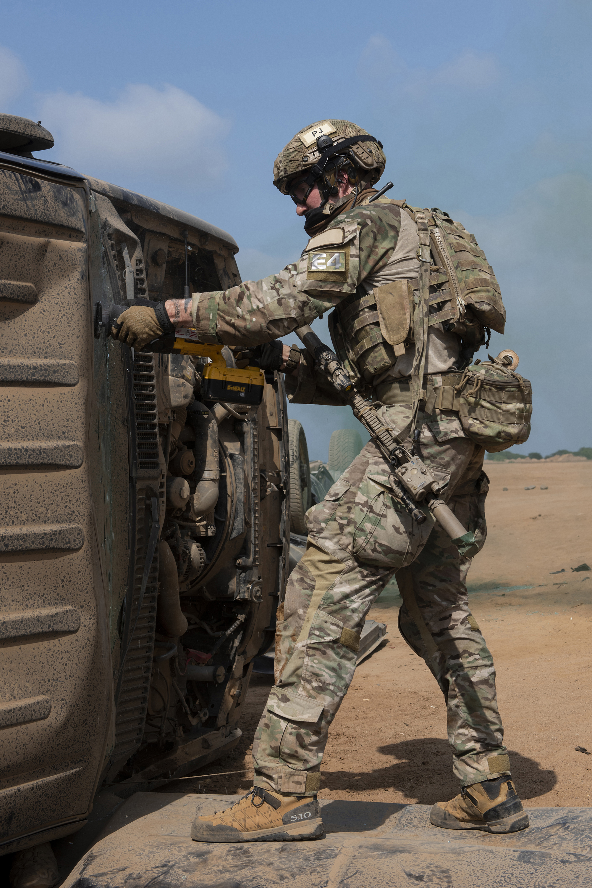A Pararescueman from the 82nd Expeditionary Rescue Squadron, cuts through the windshield of an overturned vehicle in order to rescue a simulated casualty in Djibouti City, Djibouti, April 24, 2018. The Airmen conducted various extrication techniques during a joint mass casualty training exercise. (U.S. Air National Guard photo by Master Sgt. Sarah Mattison) (Portions of this image were obscured for security reasons)