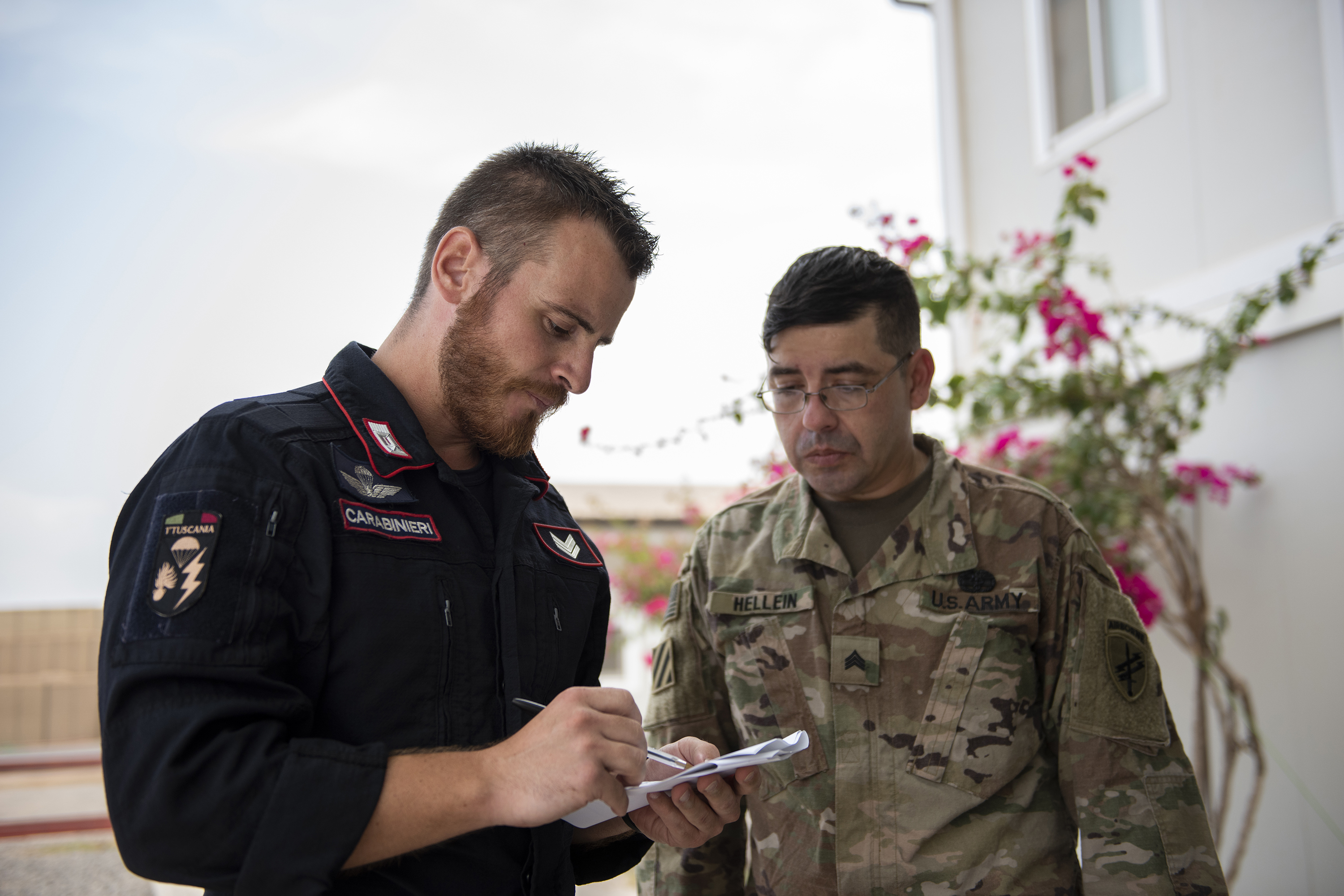 U.S. Army Sgt. Richard Hellein, a combat medic with the 404th Civil Affairs Battalion Functional Specialty Team, observes as Italian Vice-brigadiere Dennis Xamin, a carabinieri with the 1st Paratroopers Carabinieri Regiment, Tuscania, reviews the steps of calling in a nine-line medical evacuation request during a Combat Lifesaver Course on Base Militar Italiano de Supporte, Djibouti, April 28, 2018. The medics were overseeing the combat lifesaver lanes, which are the final task for the students prior to completion of the course. (U.S. Air National Guard photo by Master Sgt. Sarah Mattison)