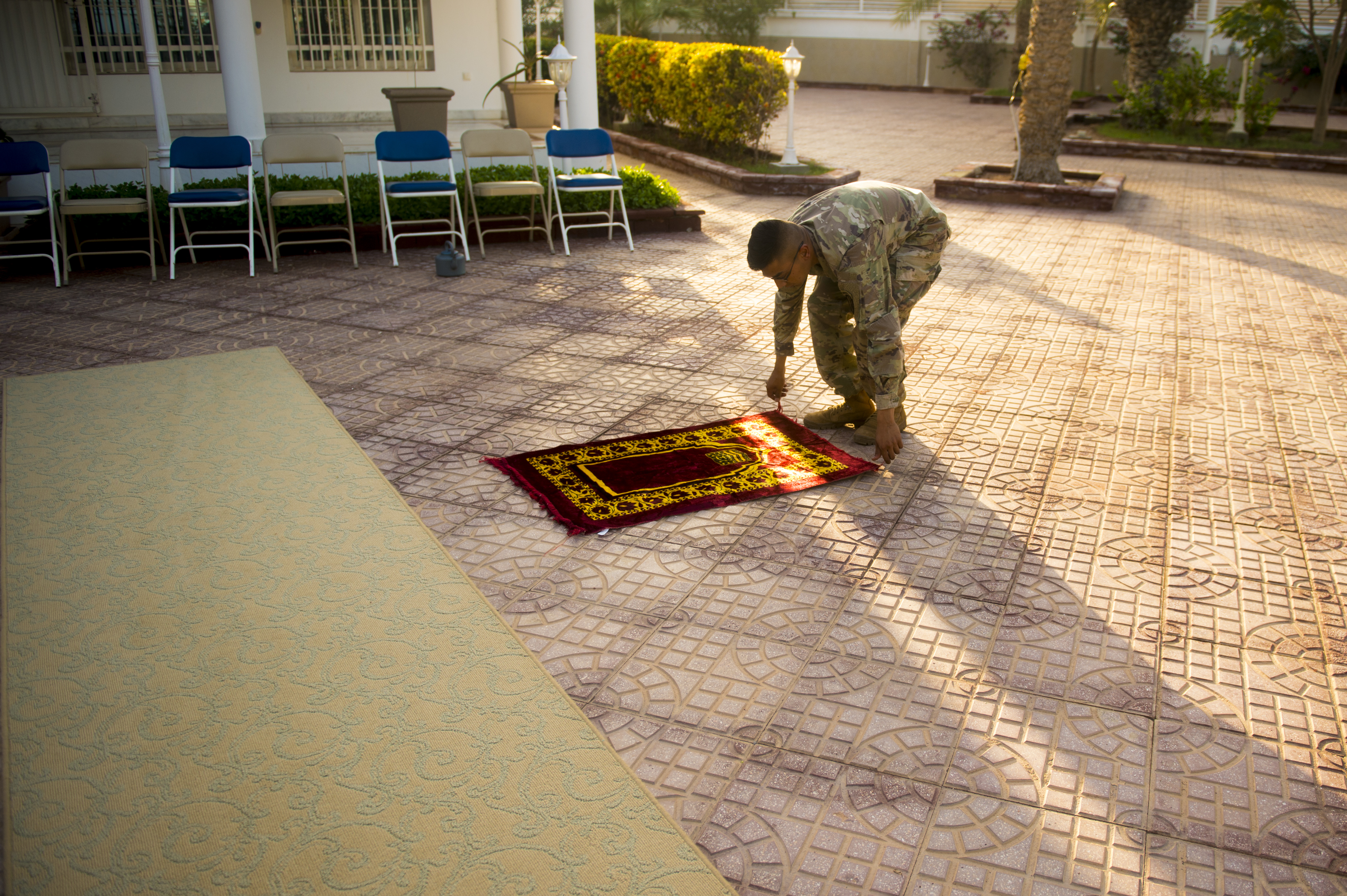 U.S. Army Specialist Ahmed Azhar, an infantryman from the 10th Mountain Division, prepares a prayer rug in during an Iftar celebration at the U.S. Ambassador to the Republic of Djibouti's house in Djibouti, May 21, 2018. The U.S. Ambassador to the Republic of Djibouti, Larry André, opened his home to celebrate two Iftars, one run by the Defense Attaché Office for senior Diboutian Military and security leaders, the second for senior government, diplomatic, and business leaders (U.S. Air Force photo by Senior Airman Scott Jackson)