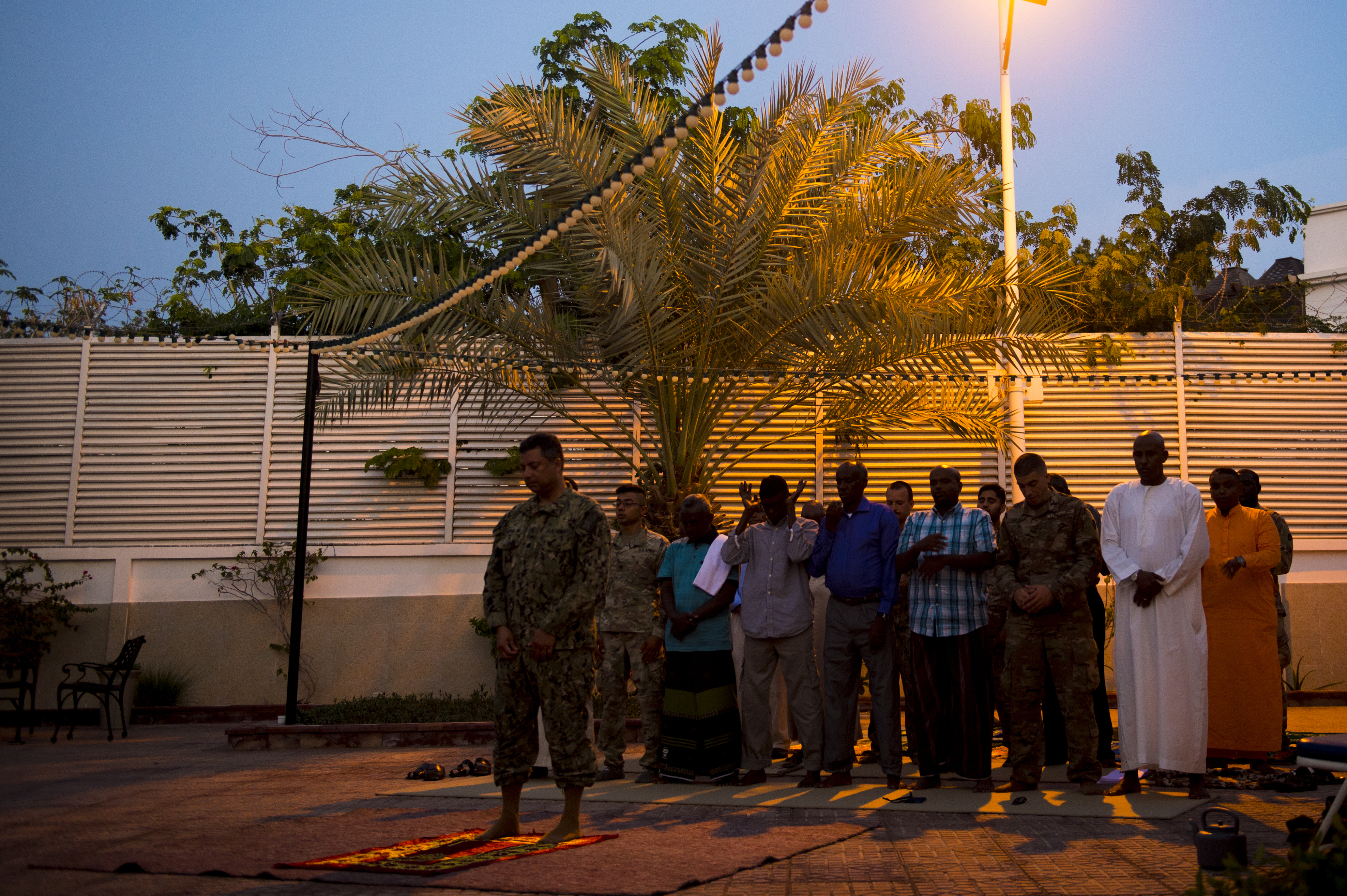 U.S. Navy Cmdr. Abduhena Saifulislam, the Deputy Command Chaplain at U.S. Africa Command, leads Muslims in prayer as the sun sets, to begin an Iftar at the residence of Larry André, the U.S. Ambassador to the Republic of Djibouti, May 21, 2018. André opened his home to celebrate two Iftars, one run by the Defense Attaché Office for senior Diboutian Military and security leaders, the second for senior government, diplomatic, and business leaders. (U.S. Air Force photo by Senior Airman Scott Jackson)