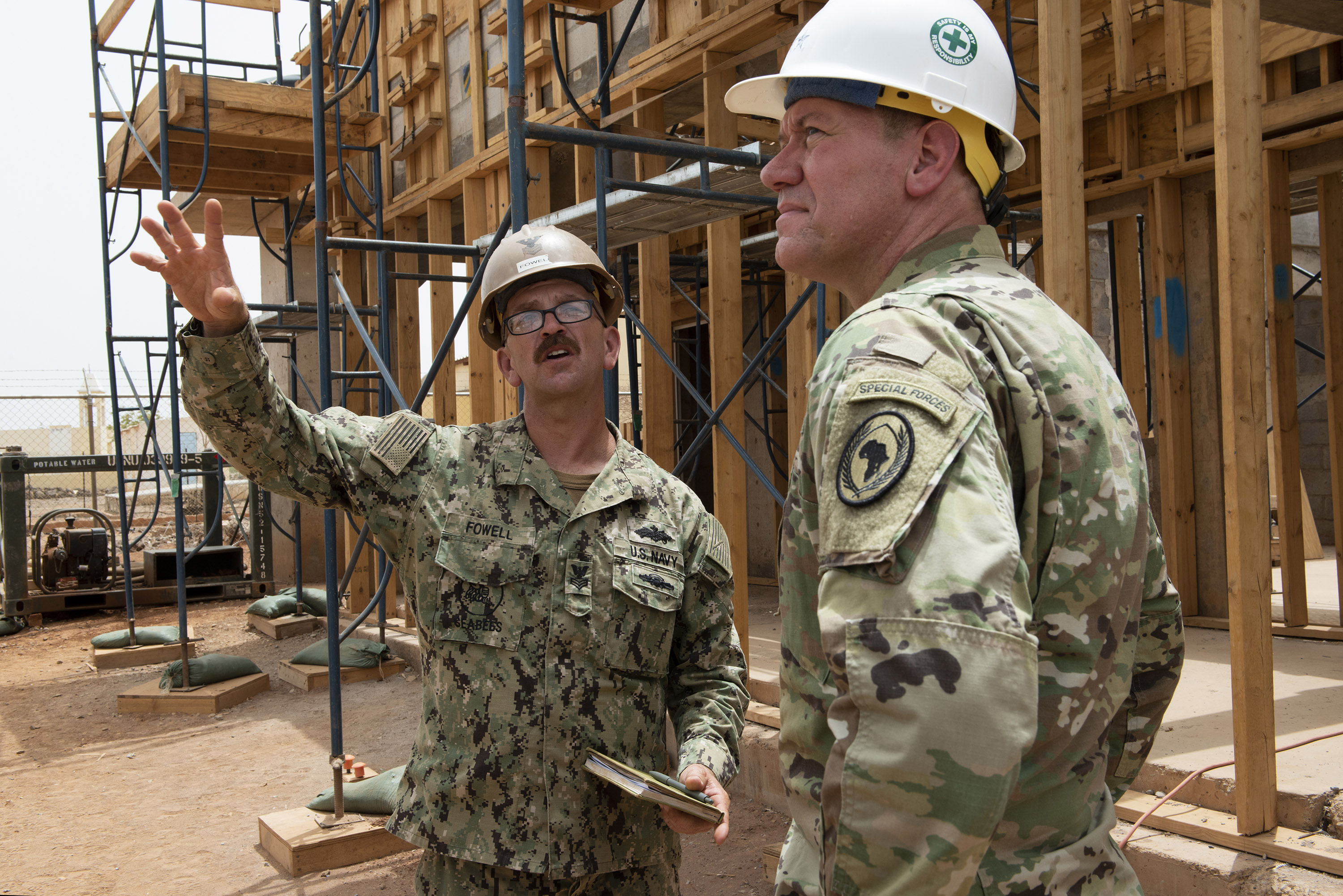 U.S. Navy Builder Petty Officer 1st Class Nathan Fowell, project supervisor, Naval Mobile Construction Battalion 11, Combined Joint Task Force - Horn of Africa, gives U.S. Army Maj. Gen. James Craig, commander, CJTF-HOA, a tour of a construction site for a medical center outside of Ali Oune, Djibouti, July 30, 2018. The completed site will include a maternity ward, a nursery and living quarters for medical staff. (U.S. Air National Guard photo by Master Sgt. Sarah Mattison)