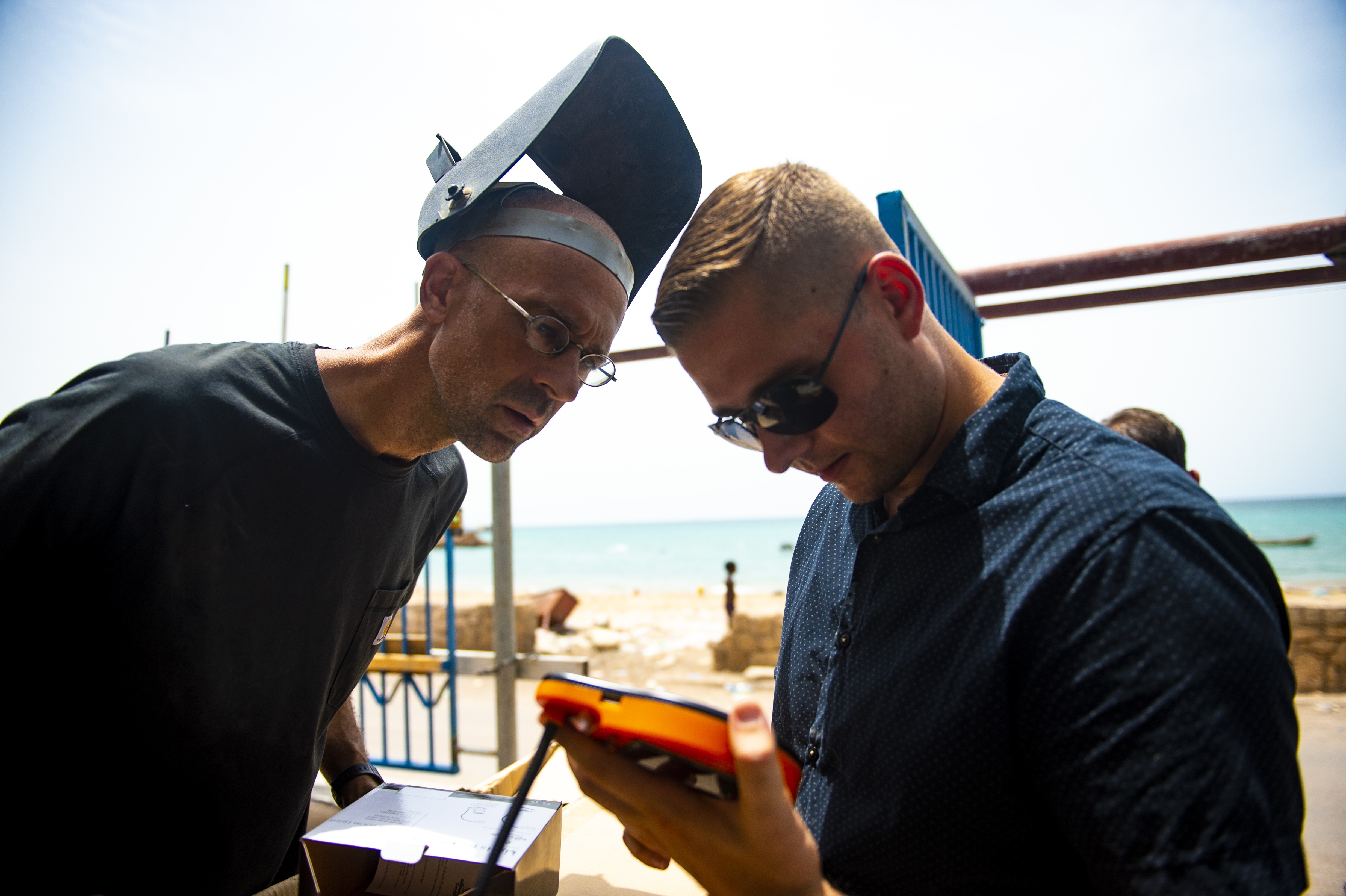 Father Mark Desser, Catholic Priest, Diocese of Djibouti, left, examines a solar powered desk light with Sgt. Kyle Caprio, 407th Civil Affairs, in Obock, Djibouti, August 17, 2018. The 407th Civil Affairs mission is to develop and maintain relationships with communities. Fr. Mark's teaches welding, stonemasonry, electrical work, plumbing, and HVAC systems in Tadjoura and Obock.  (U.S. Air Force photo by Senior Airman Scott Jackson)