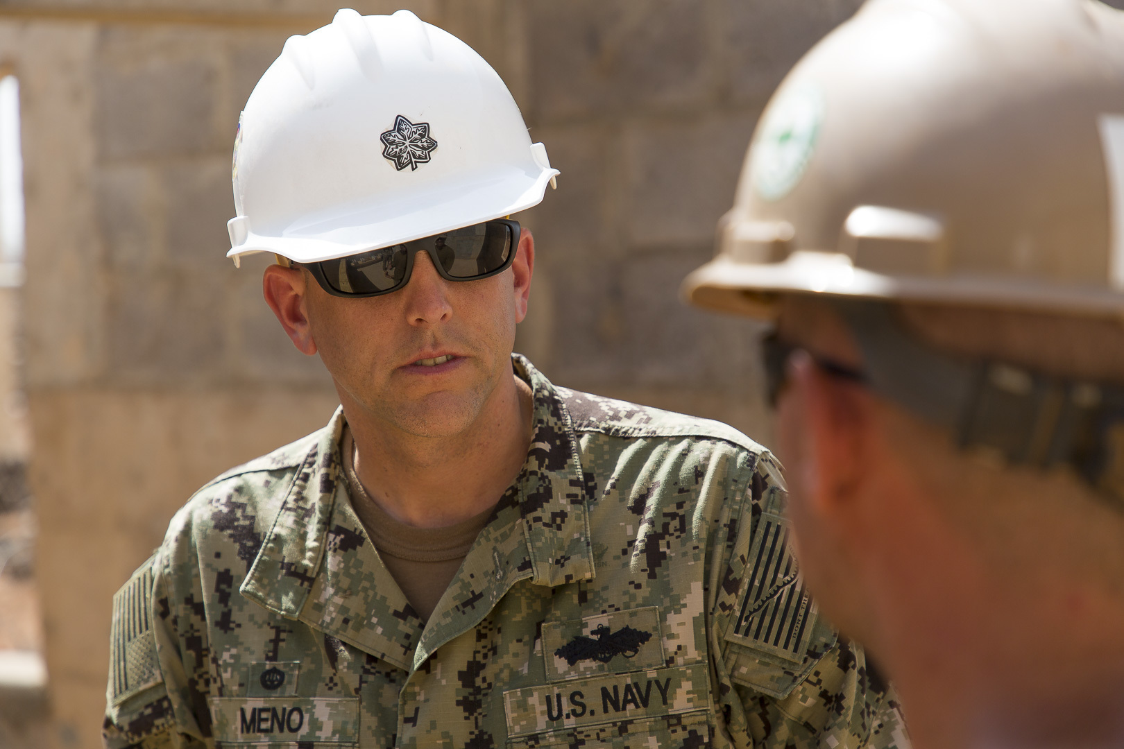 U.S. Navy Civil Engineer Corps Cmdr. Michael Meno, Naval Mobile Construction Battalion 1 commander, receives a construction site briefing from Builder 2nd Class Erik Rau in Ali Oune, Djibouti, Sept.19, 2018. Seabees with NMCB 1 Detachment Horn of Africa are building a medical facility in Ali Oune in support of the Ministry of Health for Djibouti. (U.S. Air National Guard photo by Master Sgt. Andrew Sinclair)