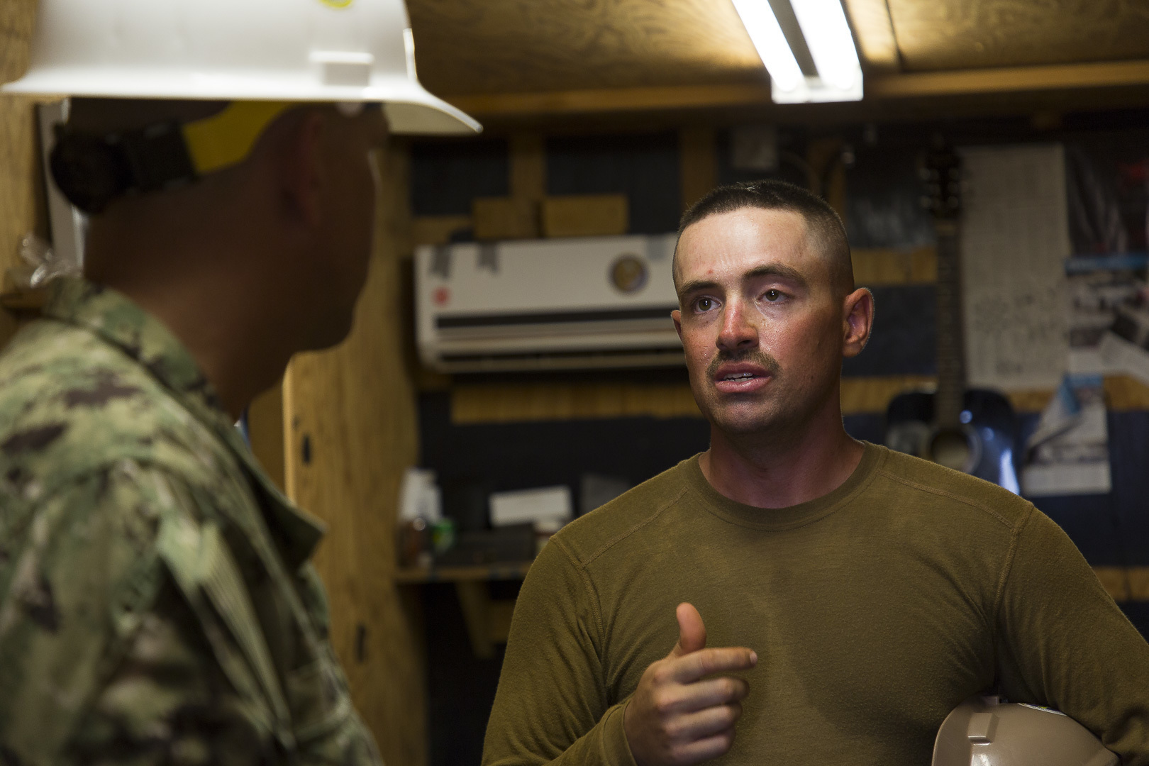 U.S. Navy Builder 2nd Class Erik Rau a Seabee assigned to Naval Mobile Construction Battalion 1 (NMCB 1) briefs Civil Engineer Corps Cmdr. Michael Meno on current on site berthing conditions in Ali Oune, Djibouti, Sept. 19, 2018. Seabees with NMCB 1 Detachment Horn of Africa are building a medical facility in Ali Oune in support of the Ministry of Health for Djibouti. (U.S. Air National Guard photo by Master Sgt. Andrew Sinclair)