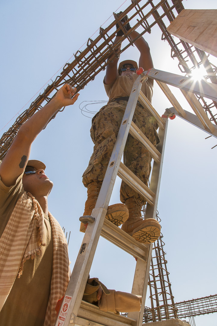 U.S. Navy Steelworker 2nd Class Timothy Vincent helps direct Construction Electrician 3rd Class Joey Sanchez, both Seabees assigned to Naval Mobile Construction Battalion 1, Detachment-Horn of Africa (NMCB 1 Det-HOA), while he ties rebar at a construction site at Ali Oune, Djibouti, Sept. 19, 2018. NMCB 1, Det-HOA is building a clinic in Ali Oune in support of the Ministry of Health for Djibouti. (U.S. Air National Guard photo by Master Sgt. Andrew Sinclair)