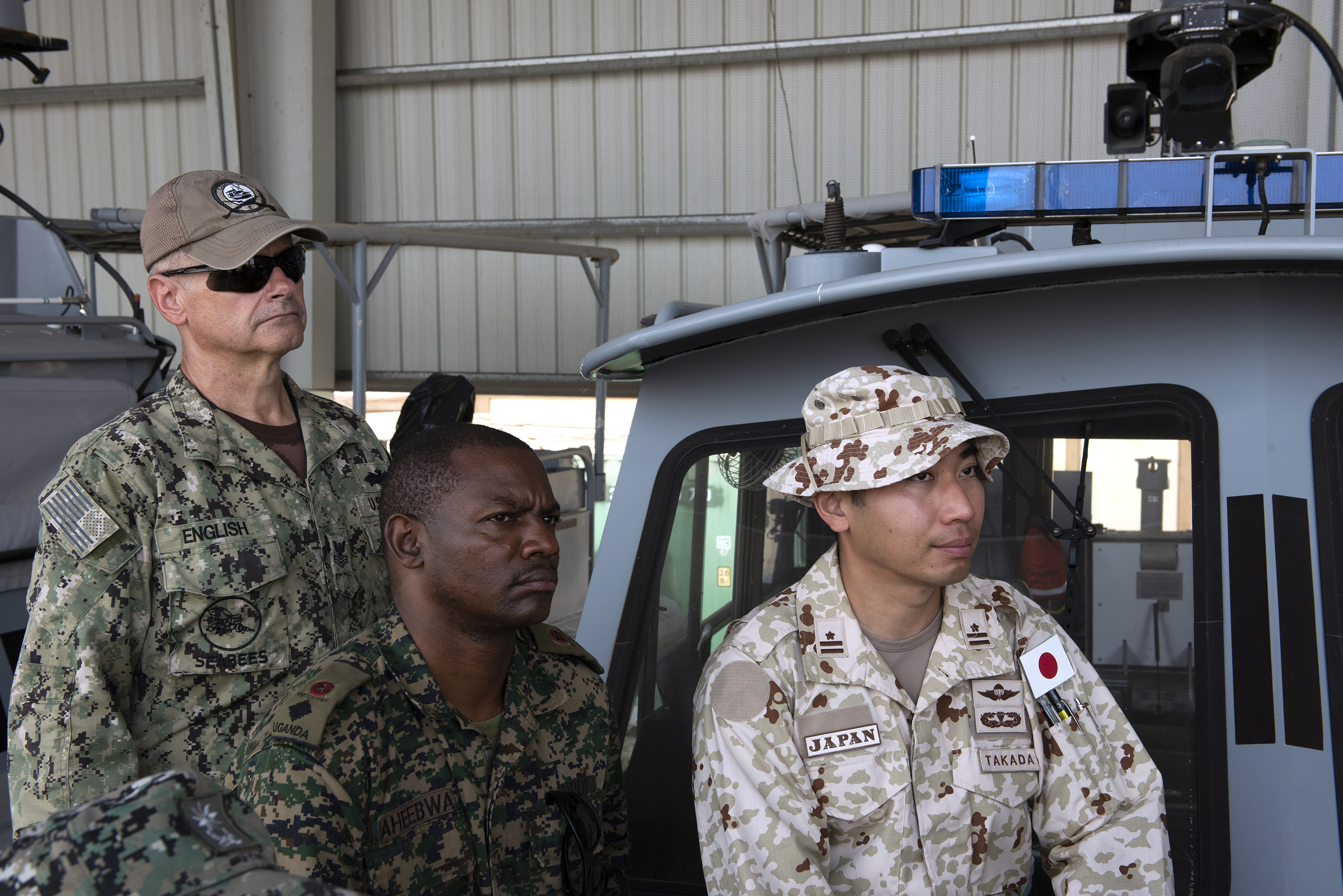 From left: U.S. Navy Construction Electrician 1st Class Richard English with Coastal Riverine Squadron 8 (CRS8), Ugandan Lt. Col. Nelson Aheebwa with the Ugandan People's Defense Force and Japanese Maj. Shinsuke Takada with the Japan Ground Self-Defense Force listen during a brief on Camp Lemonnier, Djibouti, Sept. 14, 2018. Both Aheebwa and Takada, foreign liaison officers from their respective countries assigned to Combined Joint Task Force-Horn of Africa, attended a brief on CRS 8 and toured one of their patrol boats. (U.S. Air National Guard photo by Master Sgt. Sarah Mattison)