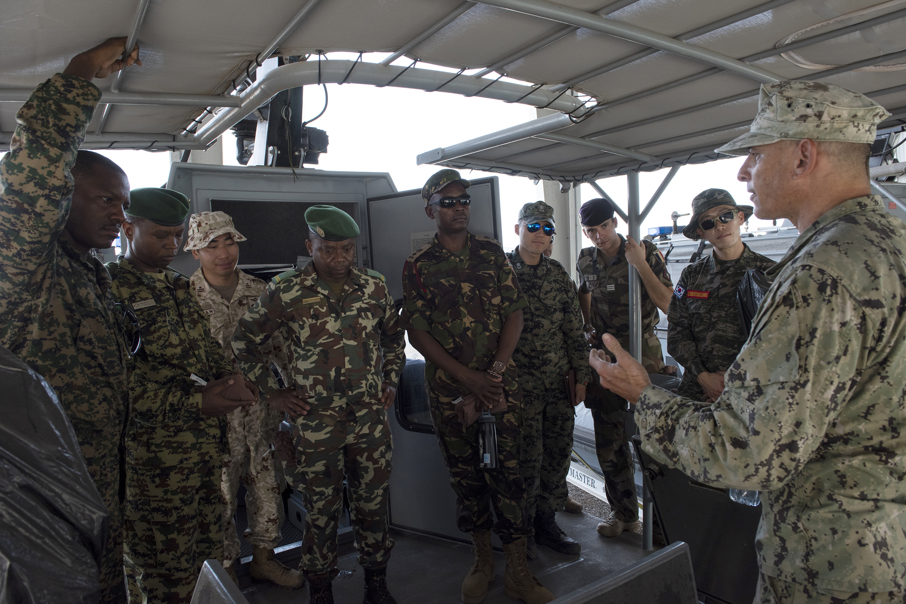 U.S. Navy Boatswain 1st Class Antonio Caia with Coastal Riverine Squadron (CRS) 8, briefs foreign liaison officers assigned to Combined Joint Task Force-Horn of Africa on Camp Lemonnier, Djibouti, Sept. 14, 2018. Caia spoke about the type of patrol boat that CRS 8 uses and gave them a tour of the boat. (U.S. Air National Guard photo by Master Sgt. Sarah Mattison)