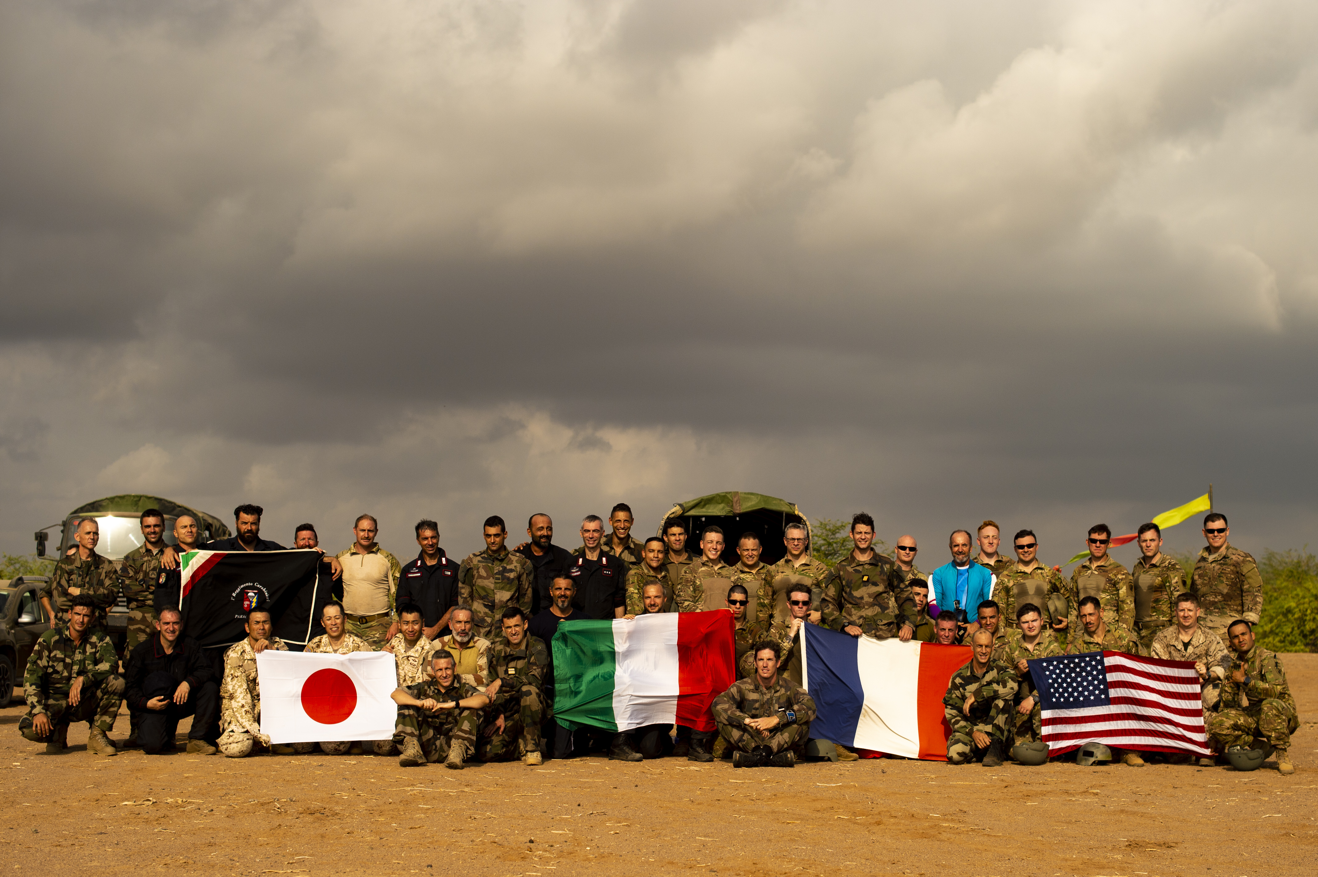 Military service members from Japan, Italy, France, and the U.S. pose for a group photograph outside Djibouti City, Djibouti, Oct. 1, 2018. American service members and coalition partners jumped together to celebrate the Feast Day of Archangel Michael, the patron saint of paratroopers. (U.S. Air Force photo by Senior Airman Scott Jackson)