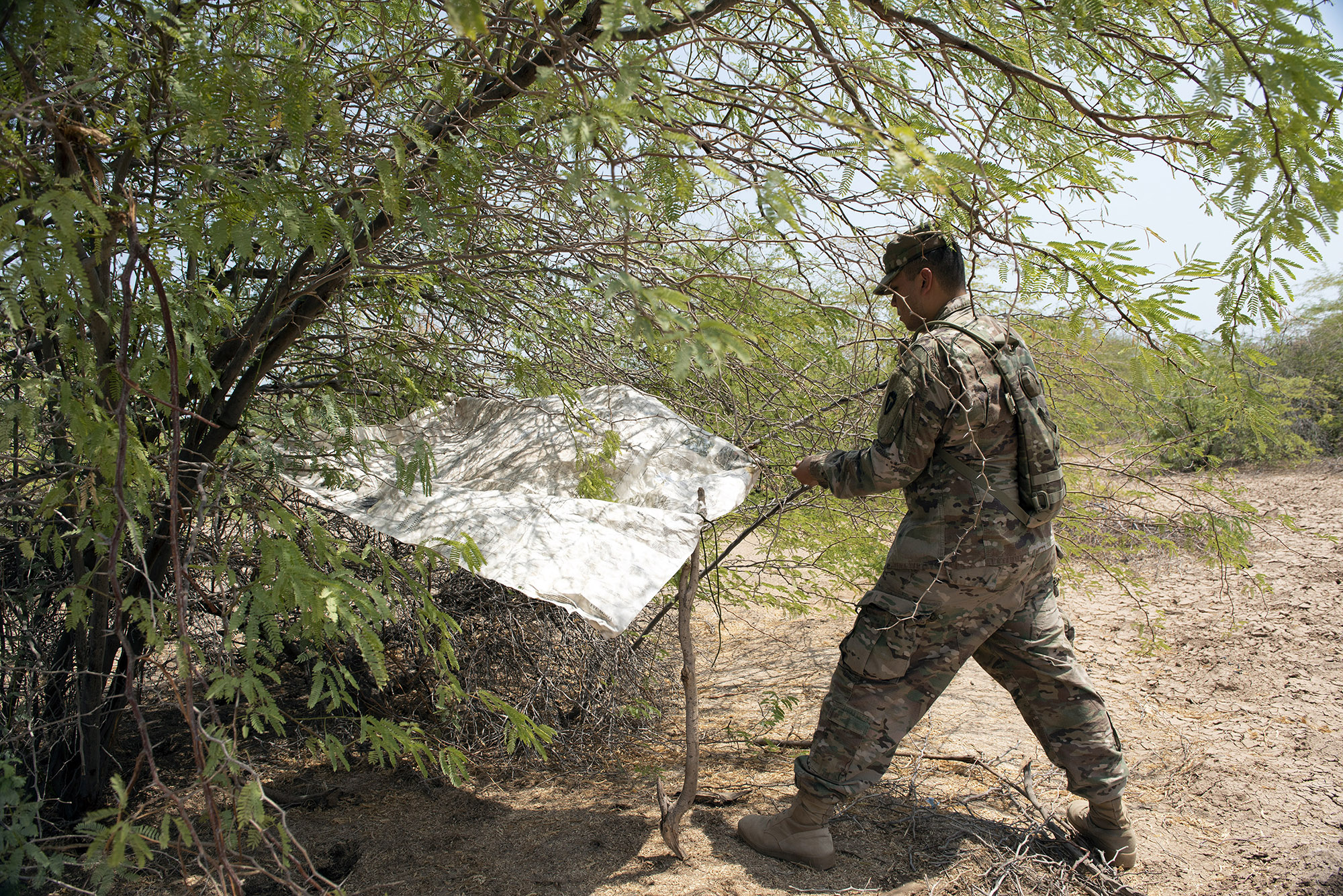 U.S. Army Pfc. Jonathan Galindo, a field artillery firefinder radar operator with 3rd Battalion, 133rd Field Artillery Regiment, Texas National Guard, uses his evasion chart and 550 cord to create a shaded shelter during a survival skills training on Camp Lemonnier, Djibouti, Oct. 13, 2018. During this training, Galindo completed various tasks such as constructing a shelter, finding alternative water sources and signaling for rescue. (U.S. Air National Guard photo by Master Sgt. Sarah Mattison)