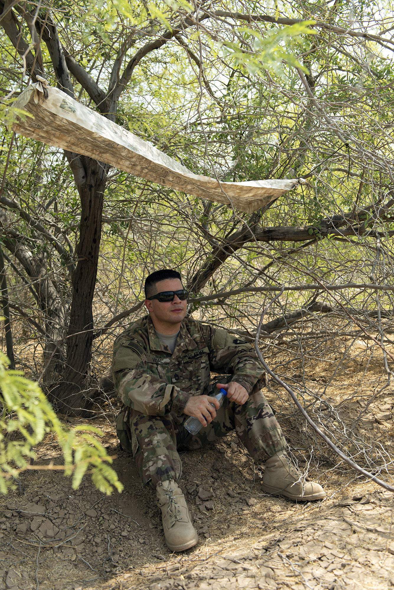 U.S. Army Sgt. 1st Class Amando Vidal, a field artillery firefinder radar operator with 3rd Battalion, 133rd Field Artillery Regiment, Texas National Guard, sits under a shaded shelter he created during survival skills training on Camp Lemonnier, Djibouti, Oct. 13, 2018. During this training, Vidal completed various tasks such as constructing a shelter, finding alternative water sources and signaling for rescue. (U.S. Air National Guard photo by Master Sgt. Sarah Mattison)