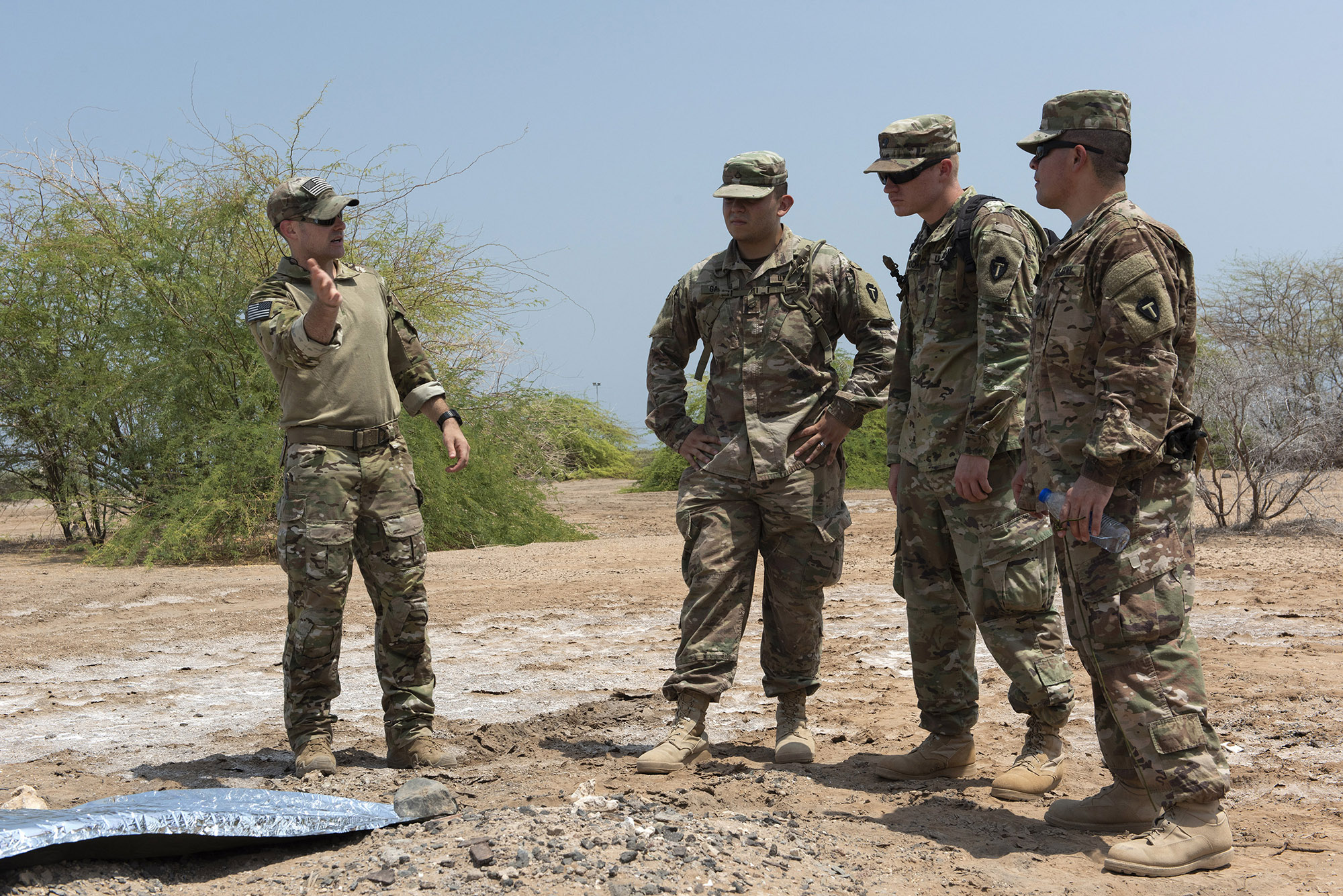 From Left: U.S. Air Force Tech. Sgt. Adam Murphy, a survival, evasion, resistance and escape specialist assigned to Combined Joint Task Force-Horn of Africa, describes how to use a mylar blanket as a hasty signaling device to U.S. Army Pfc. Jonathan Galindo, a field artillery firefinder radar operator, Spec. Killian Tooke, a radar repairer, and Sgt. 1st Class Amando Vidal, a field artillery firefinder radar operator, all assigned to 3rd Battalion, 133rd Field Artillery Regiment, Texas National Guard, during survival skills training on Camp Lemonnier, Djibouti, Oct. 13, 2018. During this training, service members performed various skills such as constructing a shelter, finding alternative water sources and signaling for rescue. (U.S. Air National Guard photo by Master Sgt. Sarah Mattison)