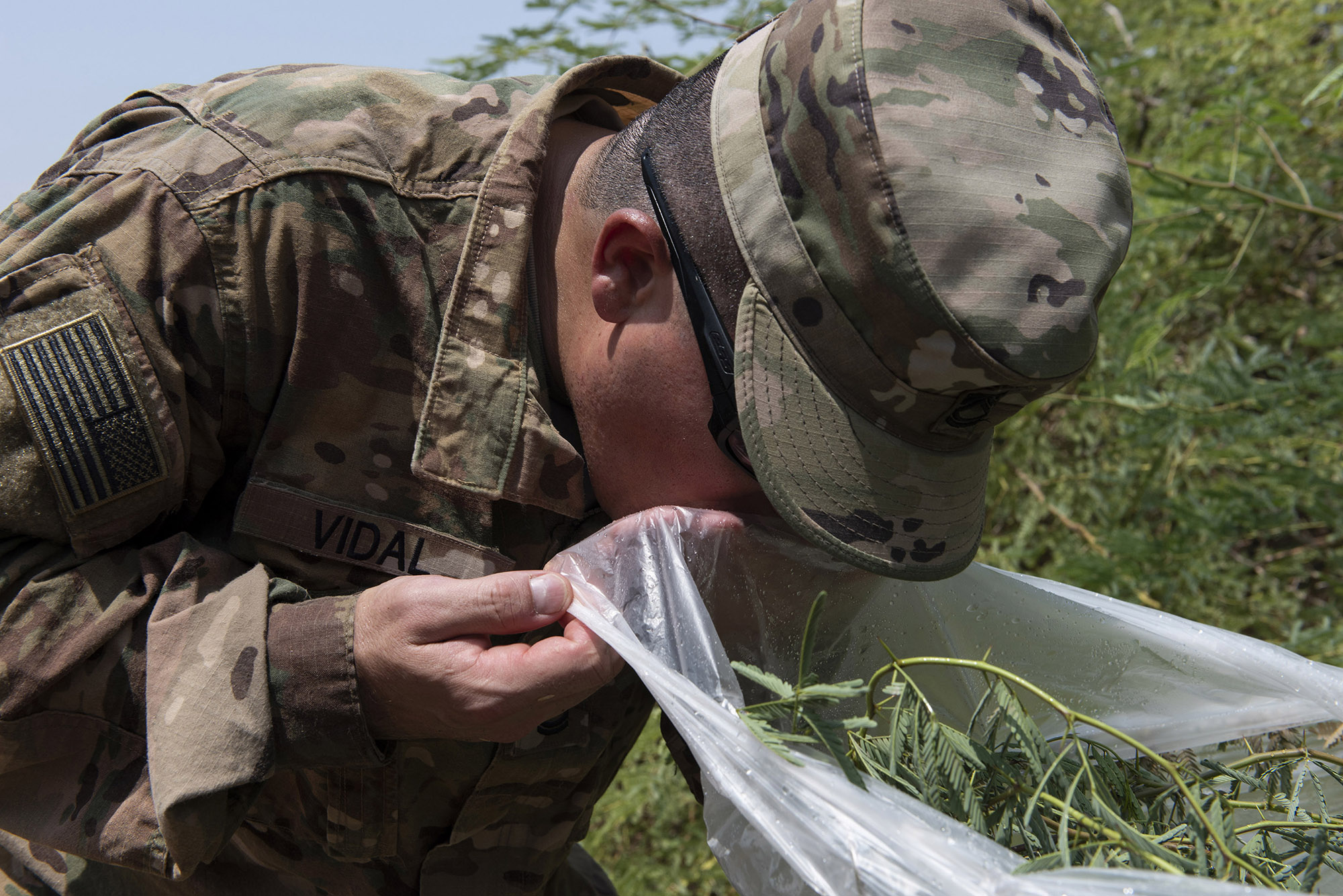 U.S. Army Sgt. 1st Class Amando Vidal, a field artillery firefinder radar operator with 3rd Battalion, 133rd Field Artillery Regiment, Texas National Guard, attempts to drink water collected during survival skills training on Camp Lemonnier, Djibouti, Oct. 13, 2018. During this training, Vidal performed various skills such as constructing a shelter, finding alternative water sources and signaling for rescue. (U.S. Air National Guard photo by Master Sgt. Sarah Mattison)