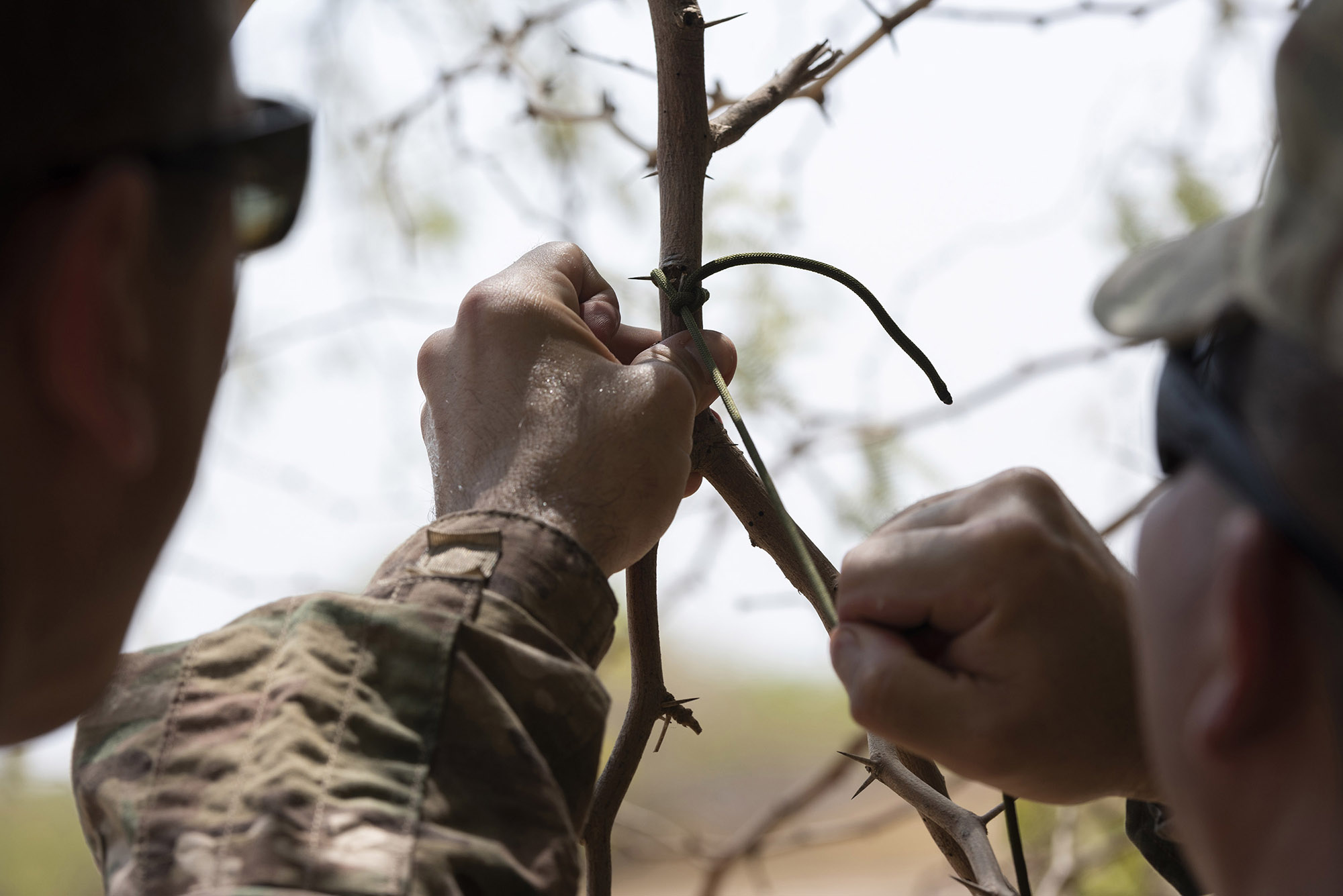 U.S. Army Sgt. 1st Class Amando Vidal, a field artillery firefinder radar operator with 3rd Battalion, 133rd Field Artillery Regiment, Texas National Guard, practices tying various types of knots during survival skills training on Camp Lemonnier, Djibouti, Oct. 13, 2018. During this training, Vidal completed various tasks such as constructing a shelter, finding alternative water sources and signaling for rescue. (U.S. Air National Guard photo by Master Sgt. Sarah Mattison)