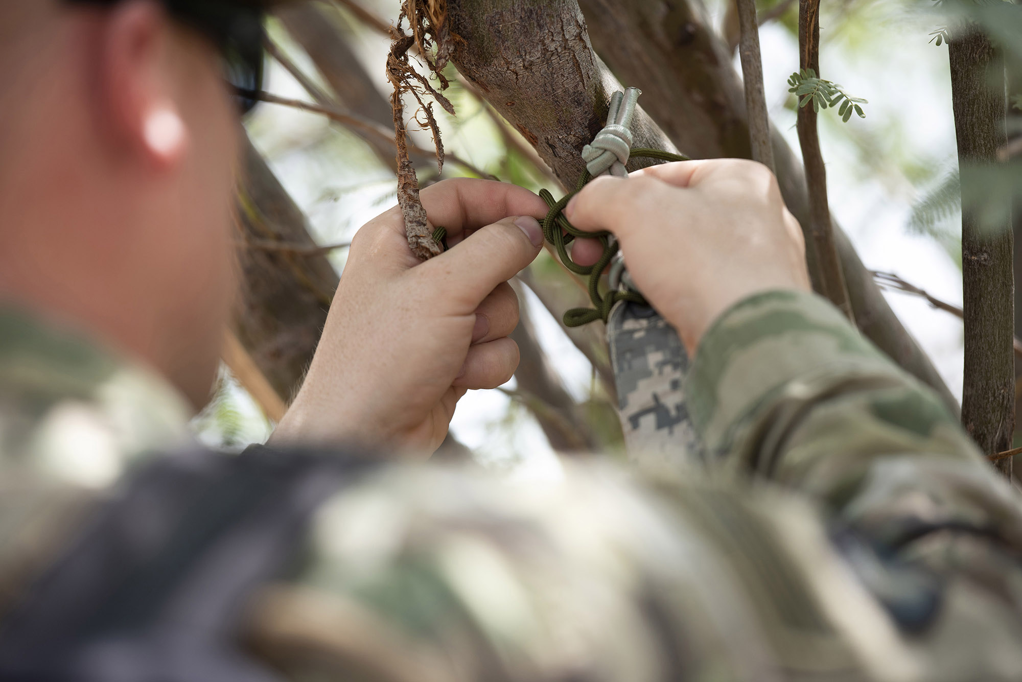 U.S. Army Spec. Killian Tooke, a radar repairer with 3rd Battalion, 133rd Field Artillery Regiment, Texas National Guard, practices tying various types of friction knots during survival skills training on Camp Lemonnier, Djibouti, Oct. 13, 2018. During this training, Tooke completed various tasks such as constructing a shelter, finding alternative water sources and signaling for rescue. (U.S. Air National Guard photo by Master Sgt. Sarah Mattison)