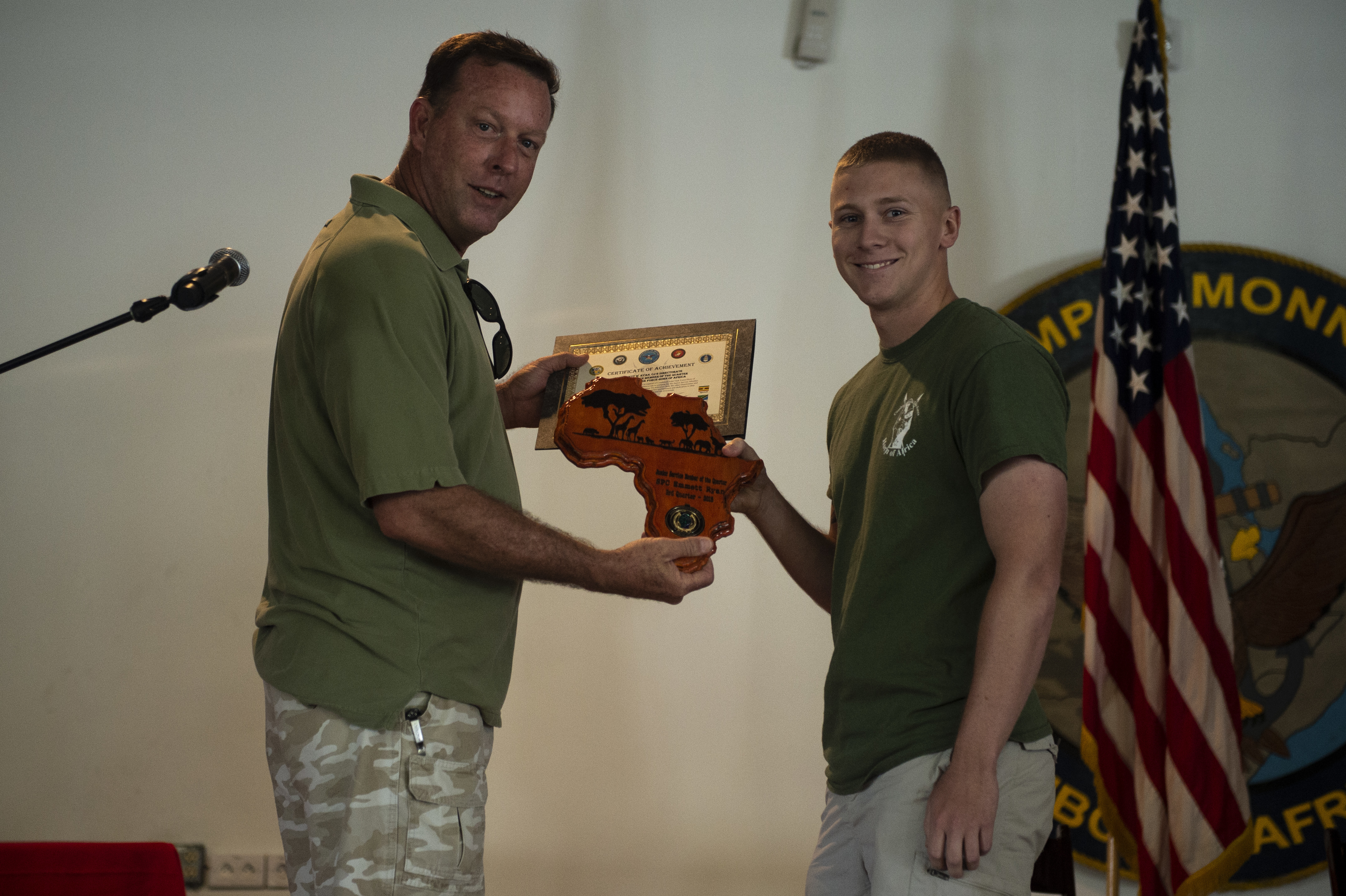 Combined Joint Task Force-Horn of Africa's Senior Enlisted Leader, Command Master Chief Karl W. Parsons, presents a quarterly award plaque and certificate to U.S. Army Spc. Emmett M. Ryan, communications specialist for CJTF-HOA, on Camp Lemonnier, Djibouti, Oct. 20, 2018. Ryan was recognized as the CJTF-HOA Junior Service Member of the Quarter during a CJTF-HOA all-hands call. (U.S. Air Force photo by Senior Airman Scott Jackson)