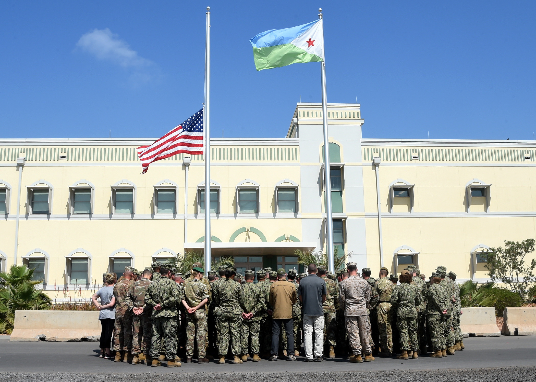 Joint forces from Combined Joint Task Force-Horn of Africa gather around the flagpoles at Camp Lemonnier, Djibouti, during a ceremony honoring the late U.S. President George H.W. Bush at Camp Lemonnier, Djibouti, Dec. 5, 2018. (U.S. Navy Photo by Mass Communication Specialist 1st Class Nick Scott/released)