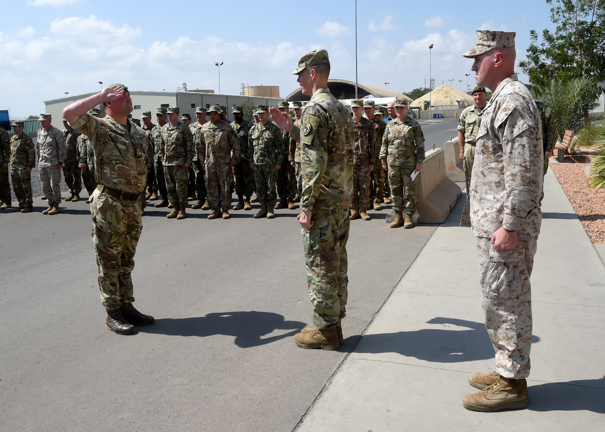 U.S. Army Brig. Gen. William L. Zana (center), deputy commander, Combined Joint Task Force-Horn of Africa (CJTF-HOA), returns the salute of British Staff Sgt. David Donovan (left), assigned to CJTF-HOA during a ceremony honoring U.S. President George H.W. Bush at Camp Lemonnier, Djibouti, Dec. 5, 2018. (U.S. Navy Photo by Mass Communication Specialist 1st Class Nick Scott/released)
