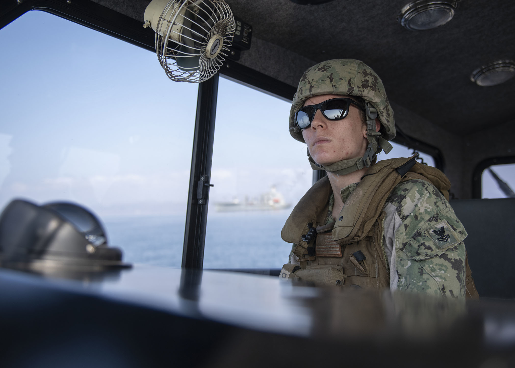 U.S. Navy Petty Officer 2nd Class Morgan Cushing, coxswain in training, Coastal Riverine Squadron 8, Combined Joint Task Force-Horn of Africa, Camp Lemonnier, Djibouti, pilots a Rigid Hull Inflatable Boat (RHIB) while providing an armed security escort in the Gulf of Tadjourah, Dec. 7, 2018. Coastal Riverine Squadron 8 conducts force protection of strategic shipping and naval vessels operating in the inshore and coastal areas, anchorages and harbors, from bare beach to sophisticated port facilities. (U.S. Air Force photo by Tech. Sgt. Shawn Nickel)