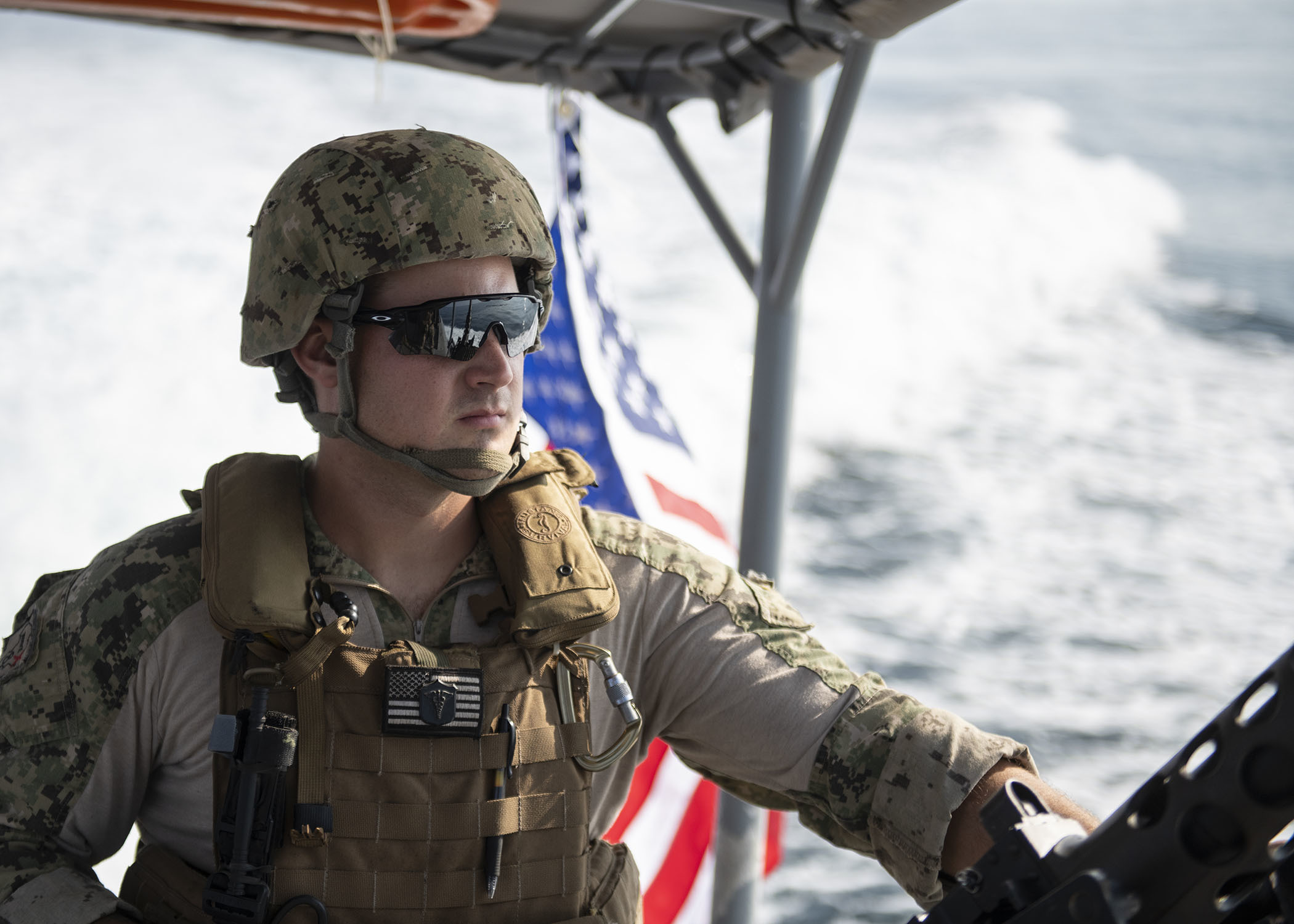 U.S. Navy Petty Officer 1st Class Alexander Weigel, engineer under instruction, Coastal Riverine Squadron 8 (CRS 8), Combined Joint Task Force-Horn of Africa, Camp Lemonnier, Djibouti, mans a security post on a Rigid Hull Inflatable Boat (RHIB) while en route to provide armed security escort in the Gulf of Tadjourah, Dec. 7, 2018. Each RHIB team in CRS 8 is made of up a diverse group of U.S. Navy Reserve Sailors with different skills and backgrounds, which aids in protecting U.S. and partner interests in the East Africa combined joint operations area. (U.S. Air Force photo by Tech. Sgt. Shawn Nickel)