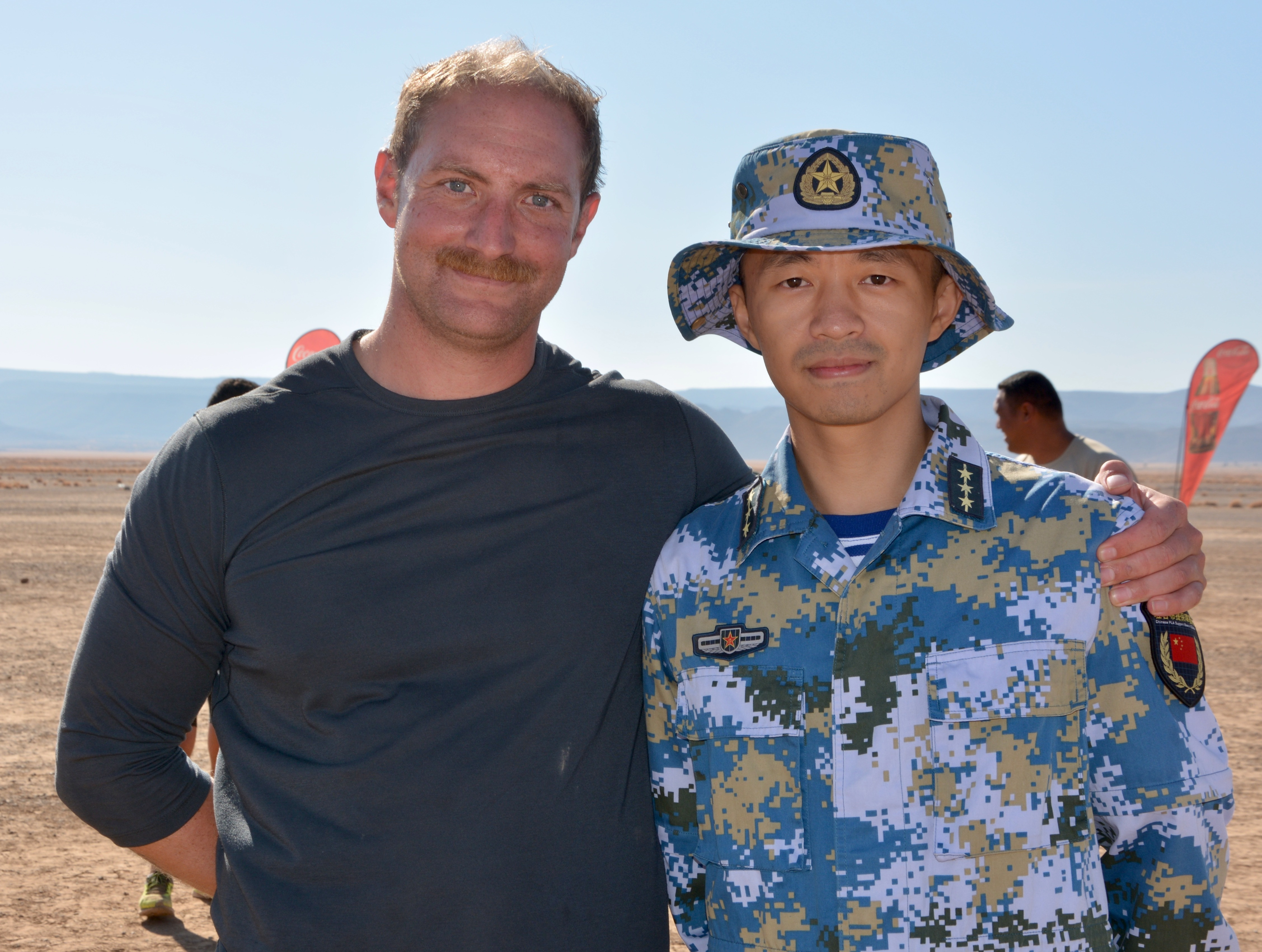A U.S. Soldier poses for a photo with an officer in the Chinese military after exchanging patches. Nearly 200 members of Combined Joint Task Force – Horn of Africa ran alongside 2,500 Djiboutian, Chinese, and coalition service members and civilians during the 15k (9.3 mile) race across a stretch of Djibouti's Grand Bara Desert, Dec. 13. (U.S. Army photo by Capt. Olivia Cobiskey)